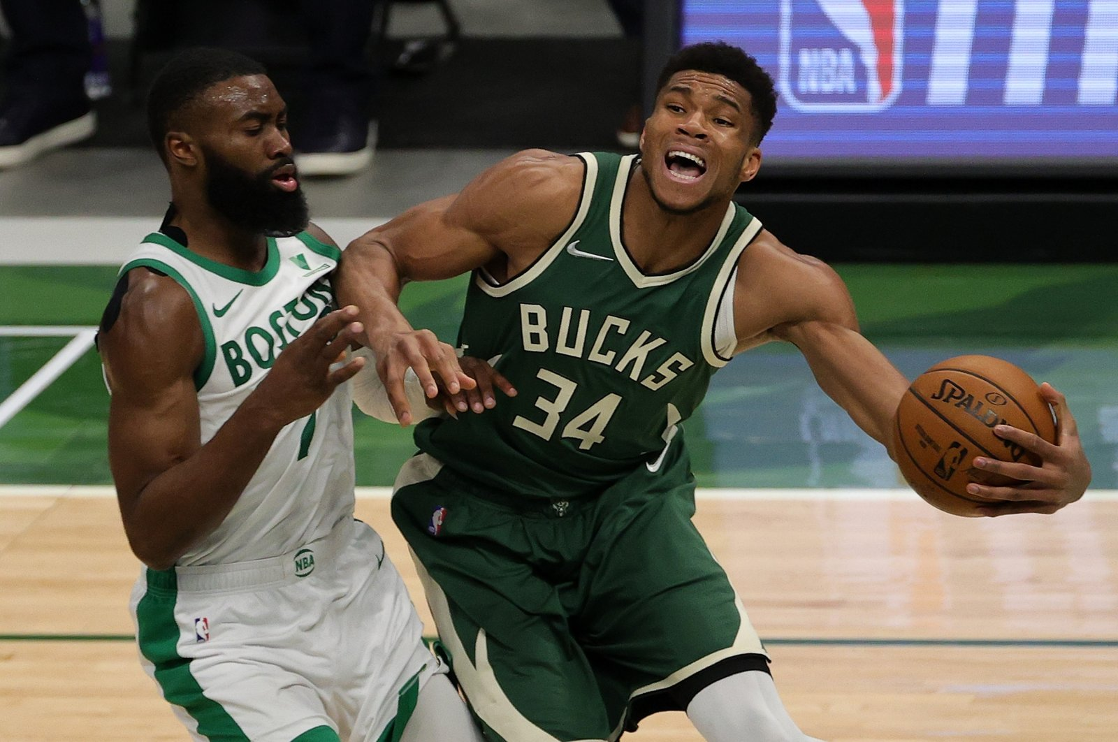 Milwaukee Bucks' Giannis Antetokounmpo (R) is defended by Boston Celtics' Jaylen Brown (L) during an NBA game at Fiserv Forum, in Milwaukee, Wisconsin, March 24, 2021. (AFP Photo)