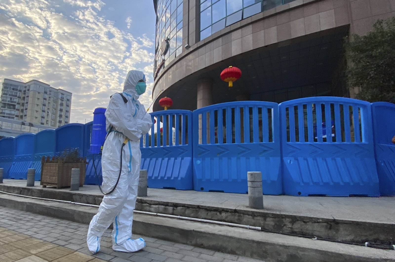 A worker in protective overalls and carrying disinfecting equipment walks outside the Wuhan Central Hospital in Wuhan, central China, Feb. 6, 2021. (AP Photo)