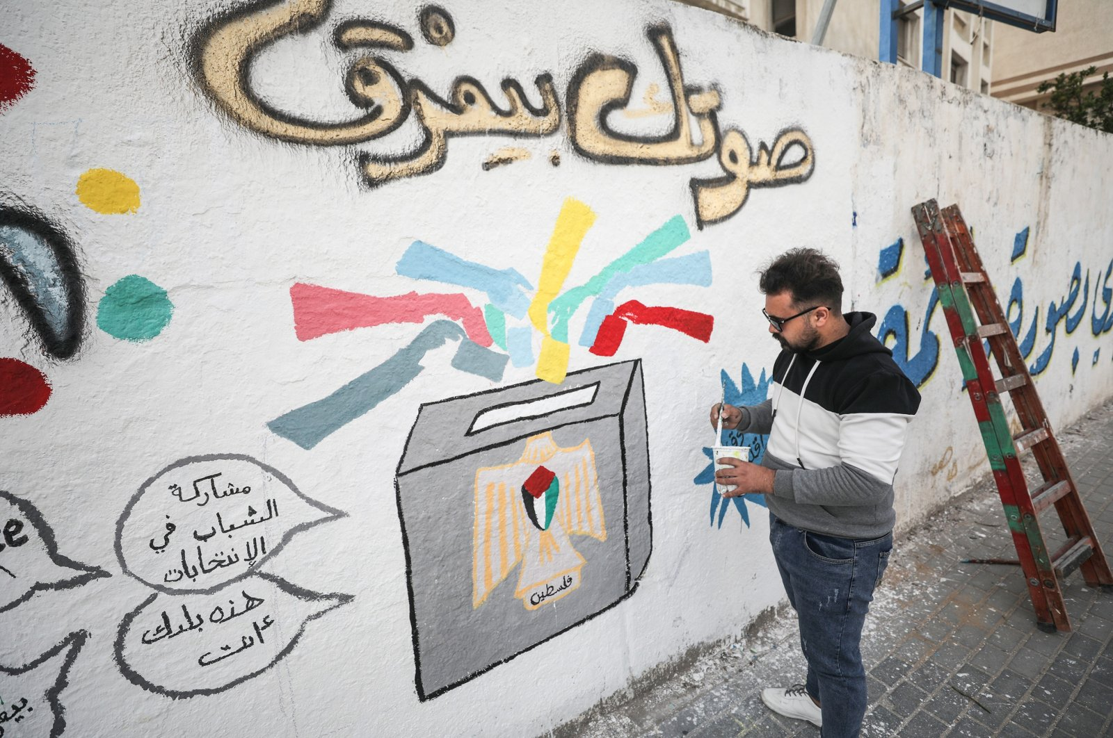 A Palestinian artist paints graffiti on a wall in the Gaza Strip to draw attention to the importance of voting in the Palestinian Legislative Council elections scheduled for May 22, Gaza, Palestine, March 24, 2021. (AA Photo)