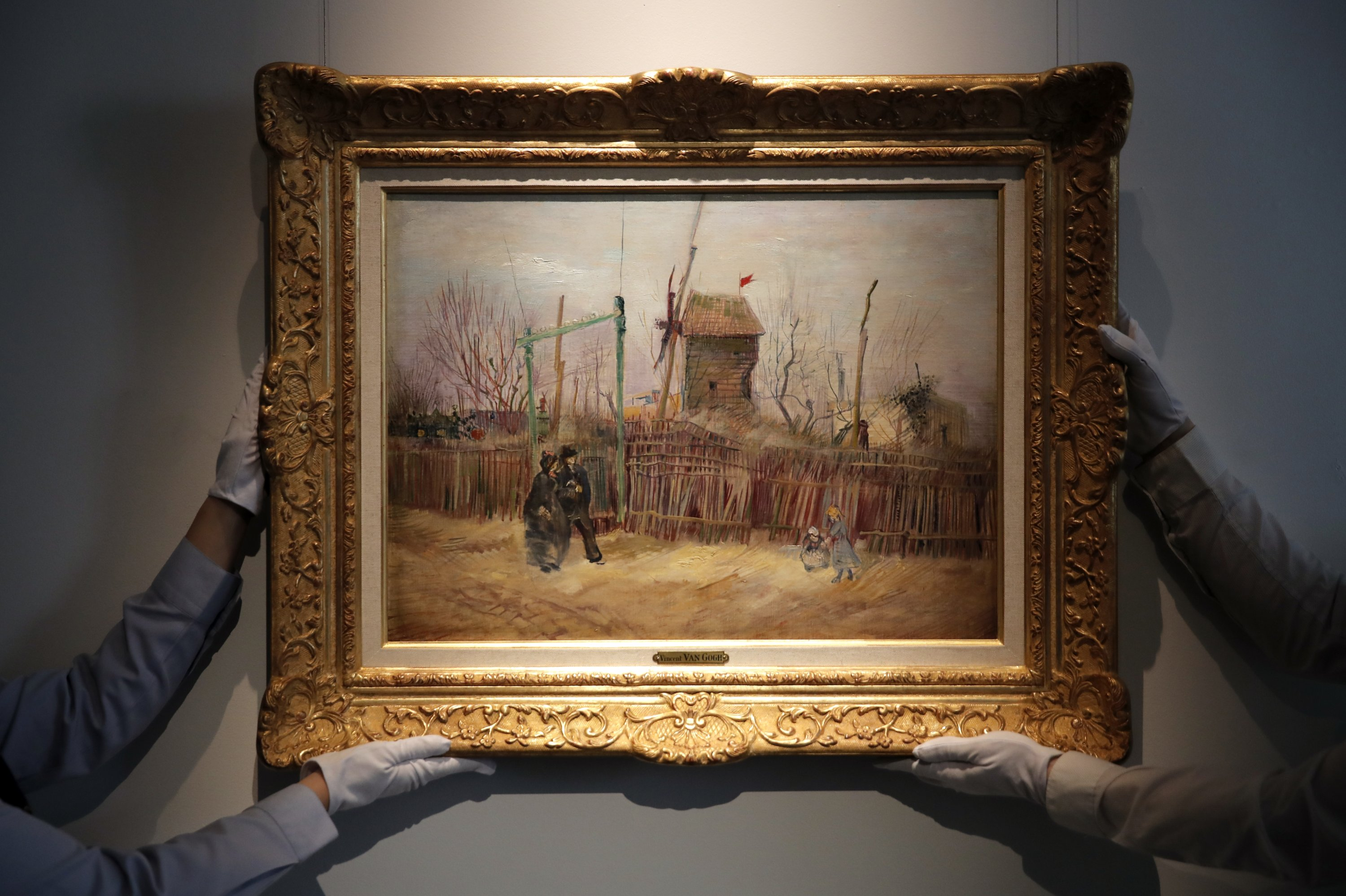 Sotheby's personnel display the 'Street scene in Montmartre' painting by Dutch master Vincent Van Gogh at Sotheby's auction house in Paris, France, Feb. 25, 2021. (AP Photo)