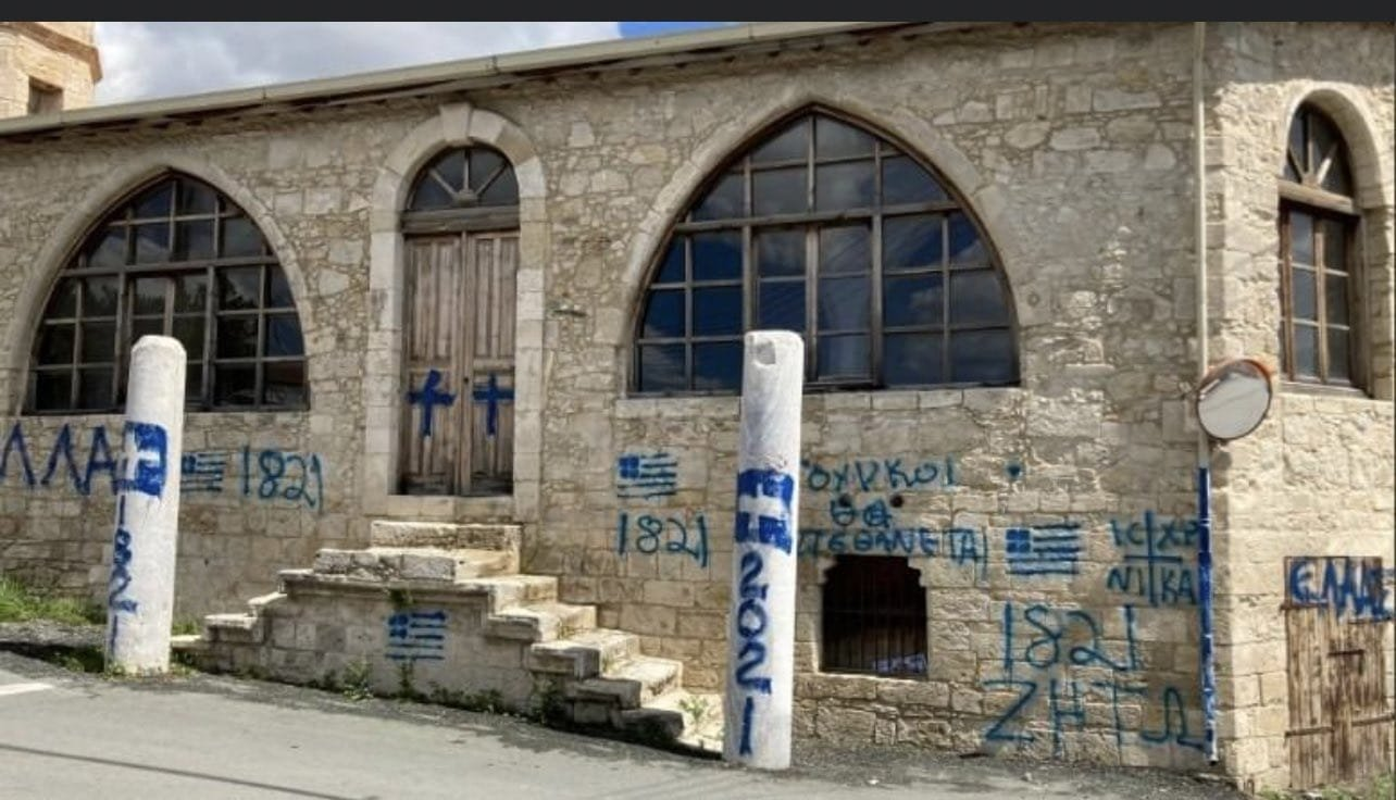 A mosque after it was vandalized by unidentified individuals who wrote slogans praising the Greek uprising on its anniversary of March 25, 1821, along with the Greek flag and a cross drawn on the walls and doors, in the village of Episkopi (Piskobu-Yalova) in Limassol, in the Greek Cypriot administration, March 25, 2021. (DHA Photo)