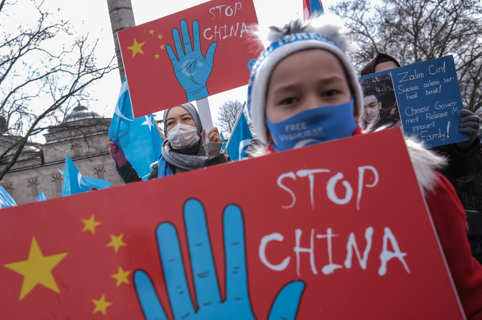 Uyghur protestors who have not heard from their families living in East Turkestan hold placards and Uyghur flags during a protest against China, in Istanbul, Turkey, March 25, 2021. (EPA Photo)