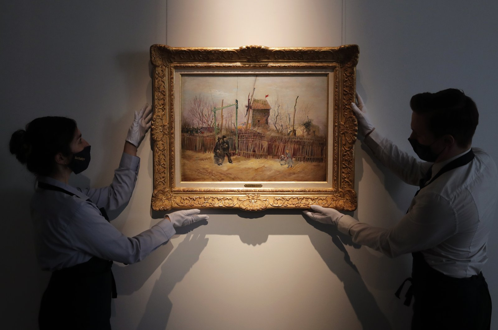"""Sotheby's personnel display the """"Street scene in Montmartre"""" painting by Dutch master Vincent Van Gogh at Sotheby's auction house in Paris, France, Feb. 25, 2021. (AP Photo)"""