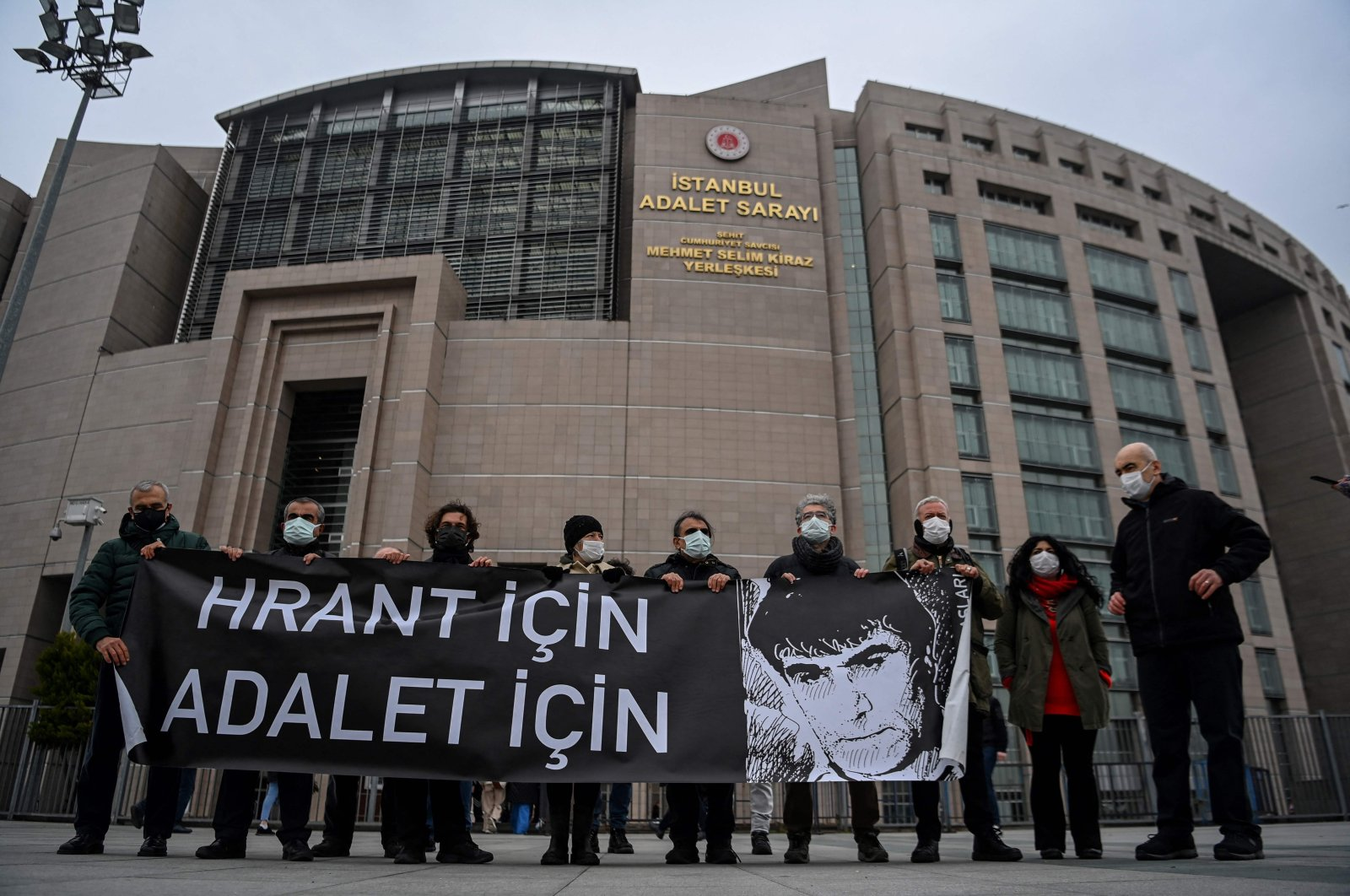 "Demonstrators hold a banner reading ""For Hrant, For Justice"" with a drawing of Hrant Dink, outside the courthouse where the trial is being held, Istanbul, Turkey, March 26, 2021. (AFP Photo)"