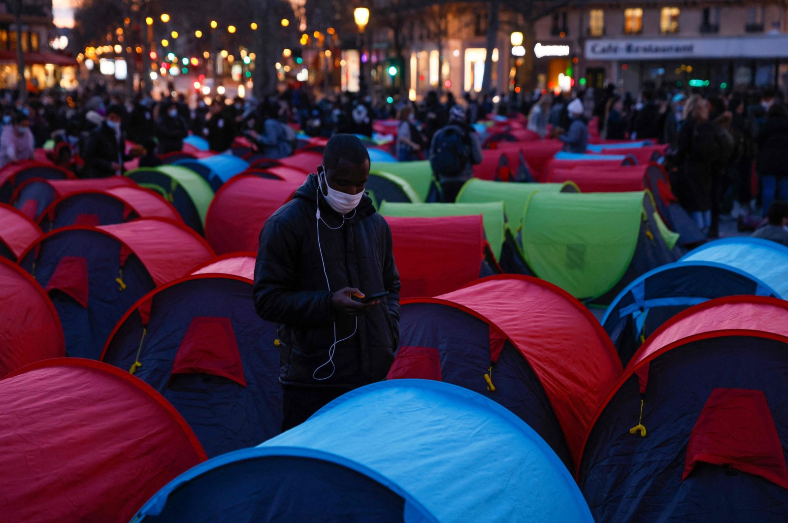 """A man looks at his mobile phone as he stands among tents set up in La Place de la Republique for the start of a """"night of solidarity"""" to highlight the plight of the homeless in central Paris, March 25, 2021. (AFP Photo)"""