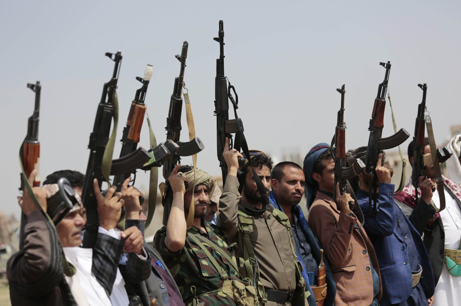 Tribesmen loyal to the Houthis raise their weapons during a protest against the agreement to establish diplomatic relations between Israel and the United Arab Emirates, in Sanaa, Yemen, Aug. 22, 2020. (AP Photo)