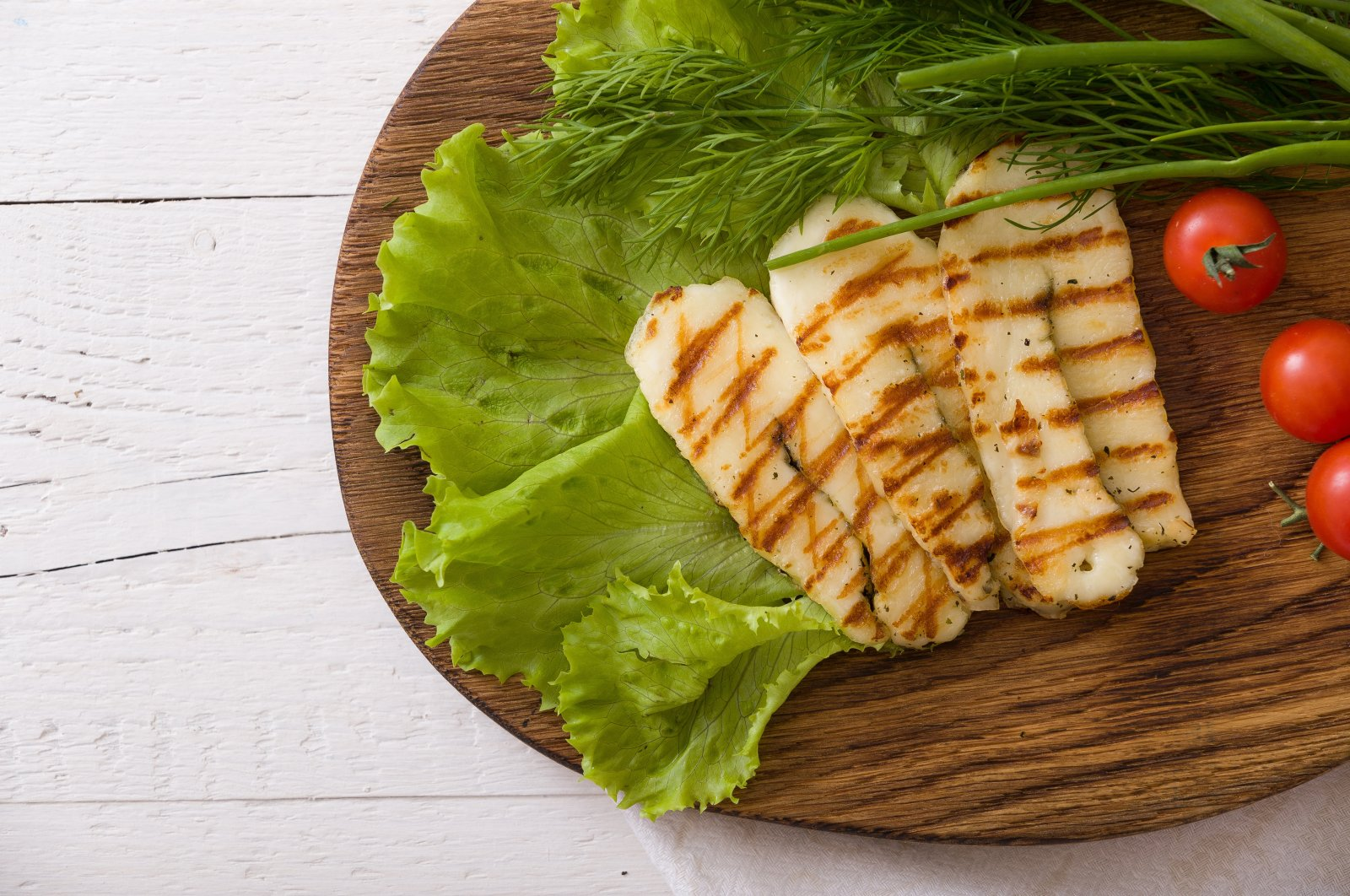 Slices of grilled halloumi cheese with green salad, fresh herbs and tomatoes. (Shutterstock Photo)