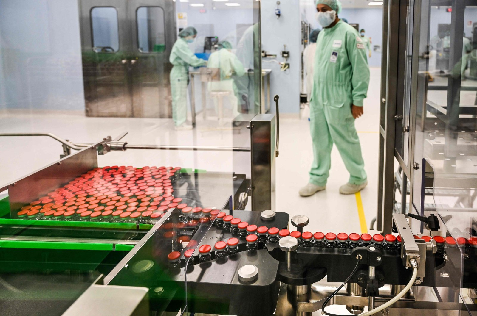 A laboratory technician supervises capped vials during filling and packaging tests for the large-scale production and supply of the University of Oxford's COVID-19 vaccine candidate, AstraZeneca at the Italian biologics' manufacturing facility of multinational corporation Catalent in Anagni, southeast of Rome, Italy, Sept. 11, 2020. (AFP Photo)