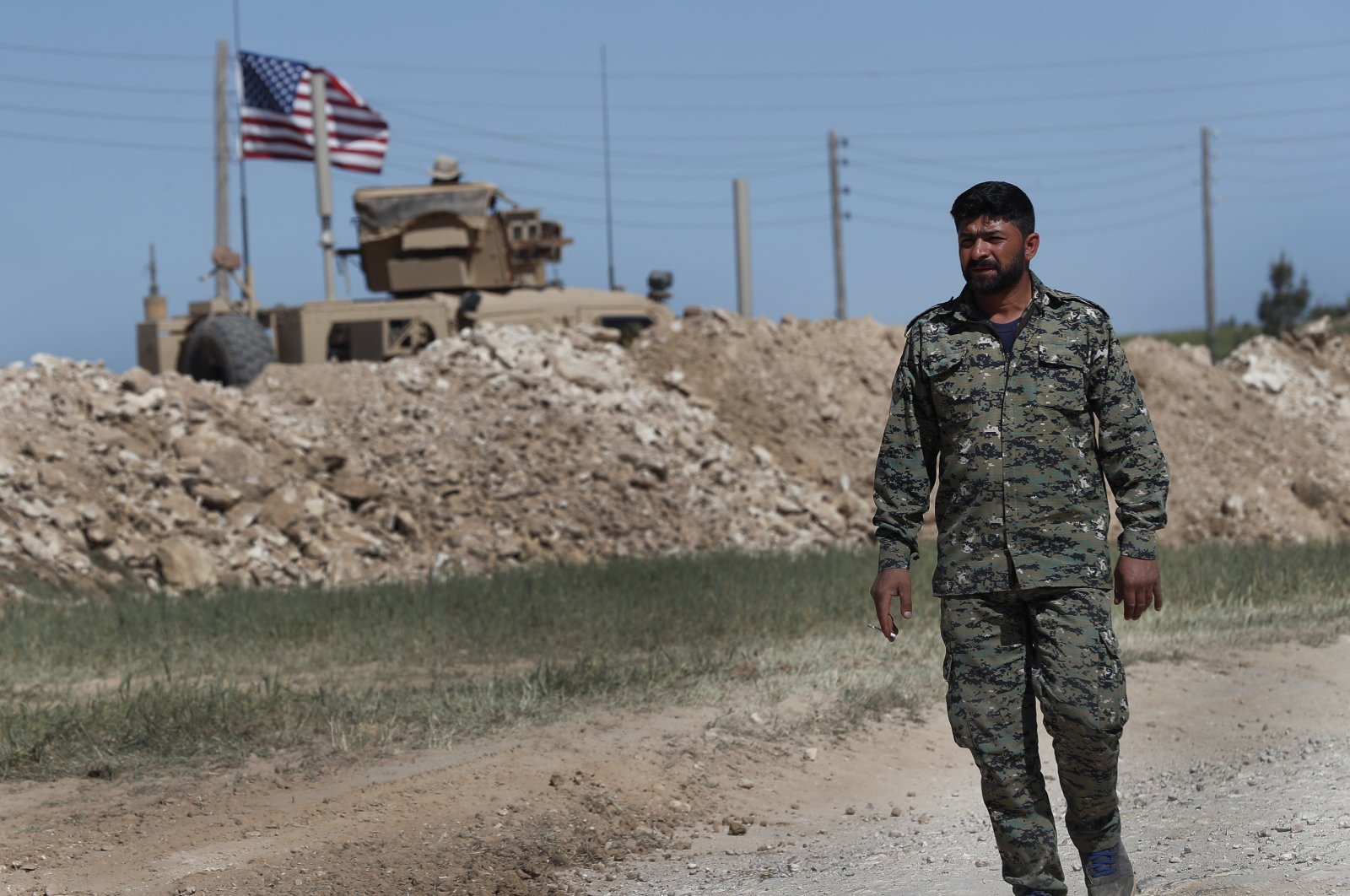 A U.S-backed YPG/PKK terrorist passes a U.S. position near the tense front line with Turkish-backed fighters, in Manbij, north Syria, April 4, 2018. (AP File Photo)