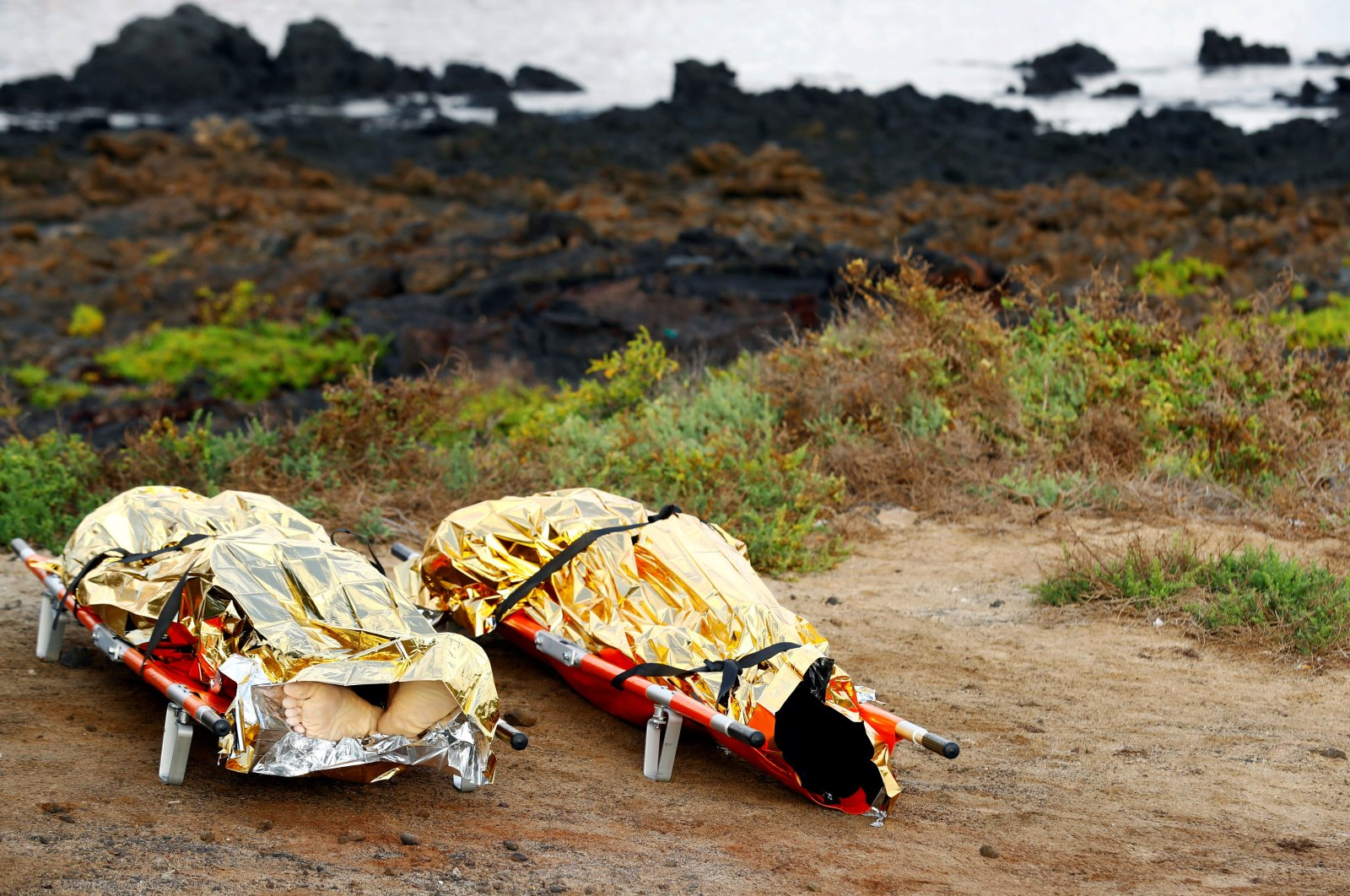 Bodies of dead people are seen on stretchers after a boat with 35 migrants from the Maghreb region capsized near the beach of Orzola, in the Canary Island of Lanzarote, Spain, Nov. 25, 2020. (Reuters File Photo)