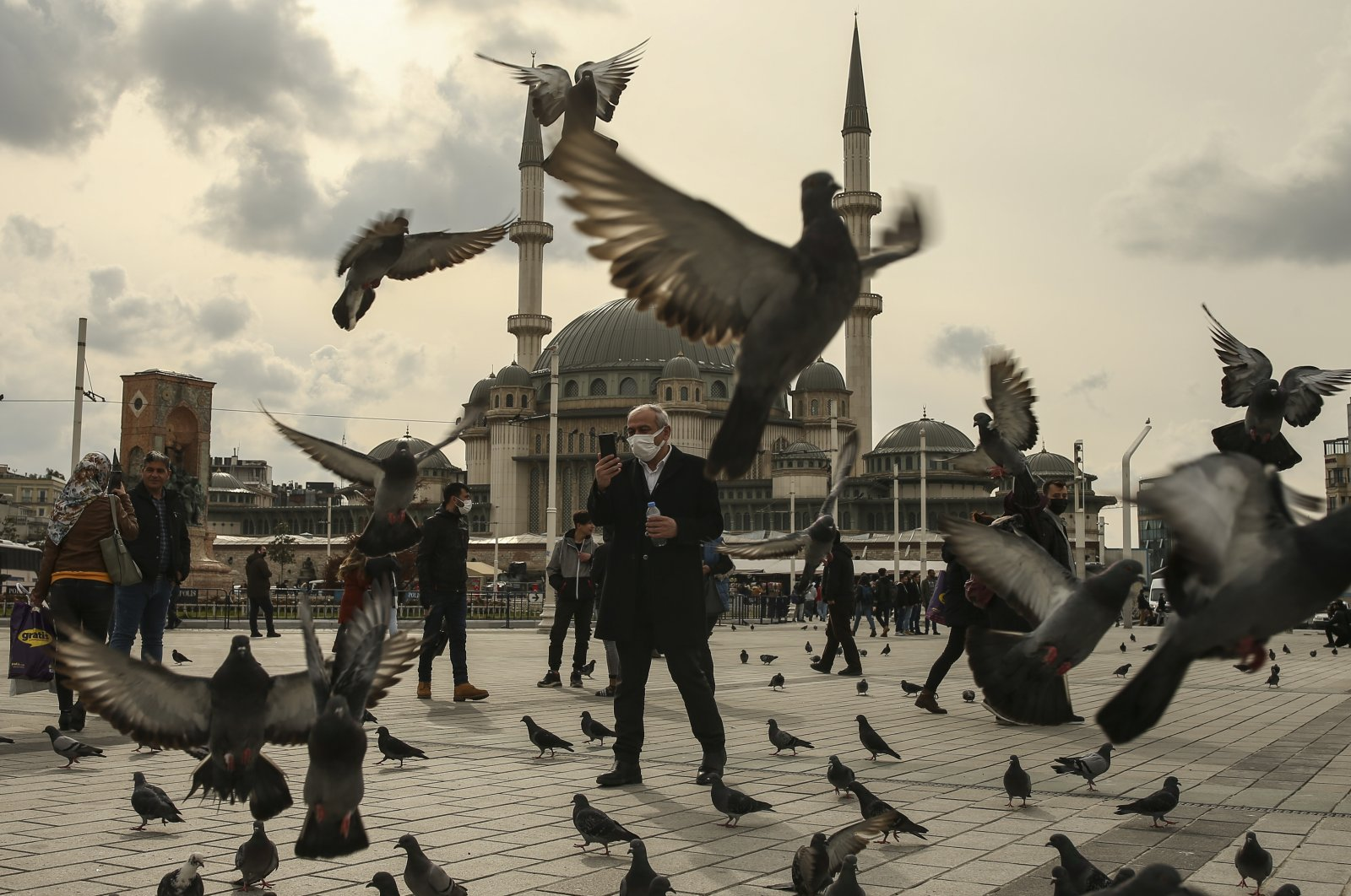 A man feeds pigeons on Taksim square in Istanbul, Thursday, March 25, 2021. (AP Photo)