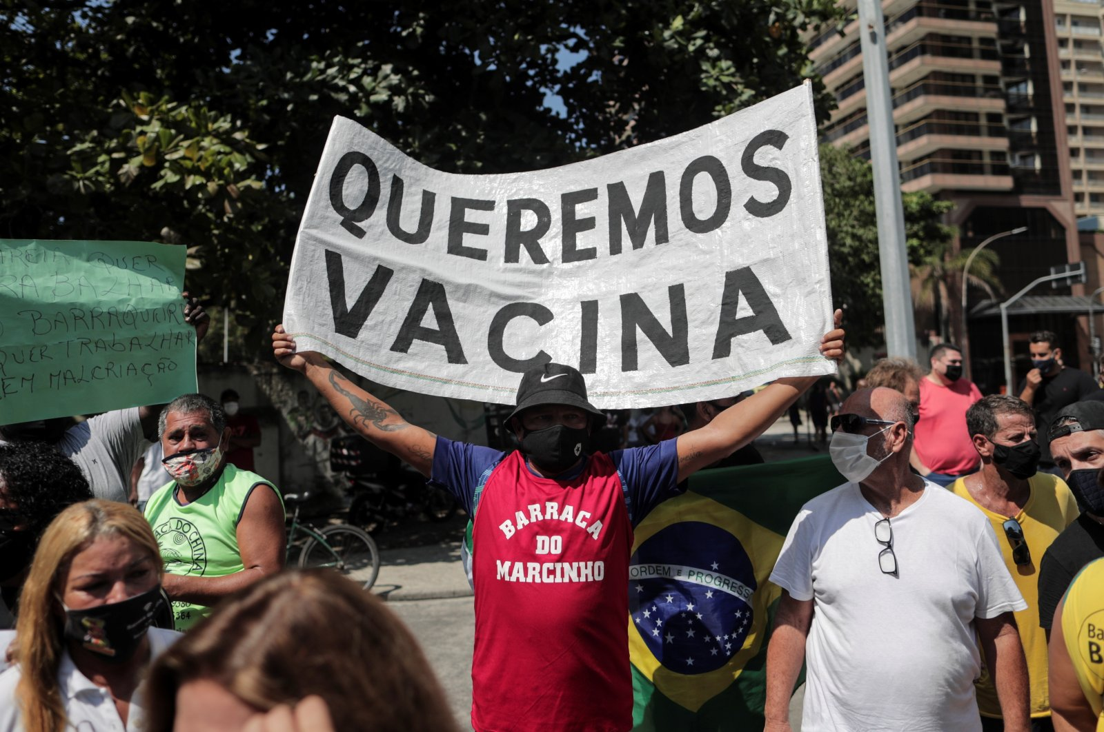 A man holds up a banner calling for a vaccine against COVID-19 during protests against the new measures implemented to stop its spread, on the beach of Copacabana, in Rio de Janeiro, Brazil, March 26, 2021.  (EPA Photo)