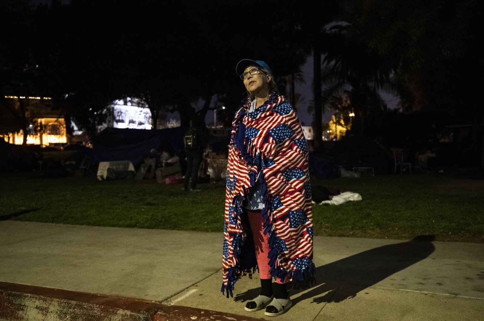 Antonia Ramirez from Mexico, experiencing homelessness for the past 20 years, stands wrapped in a blanket displaying American flags next to the tents of the homeless encampment of Echo Park Lake as a large police force is mobilized to clear the area in Los Angeles, California, U.S., March 24, 2021. (EPA Photo)