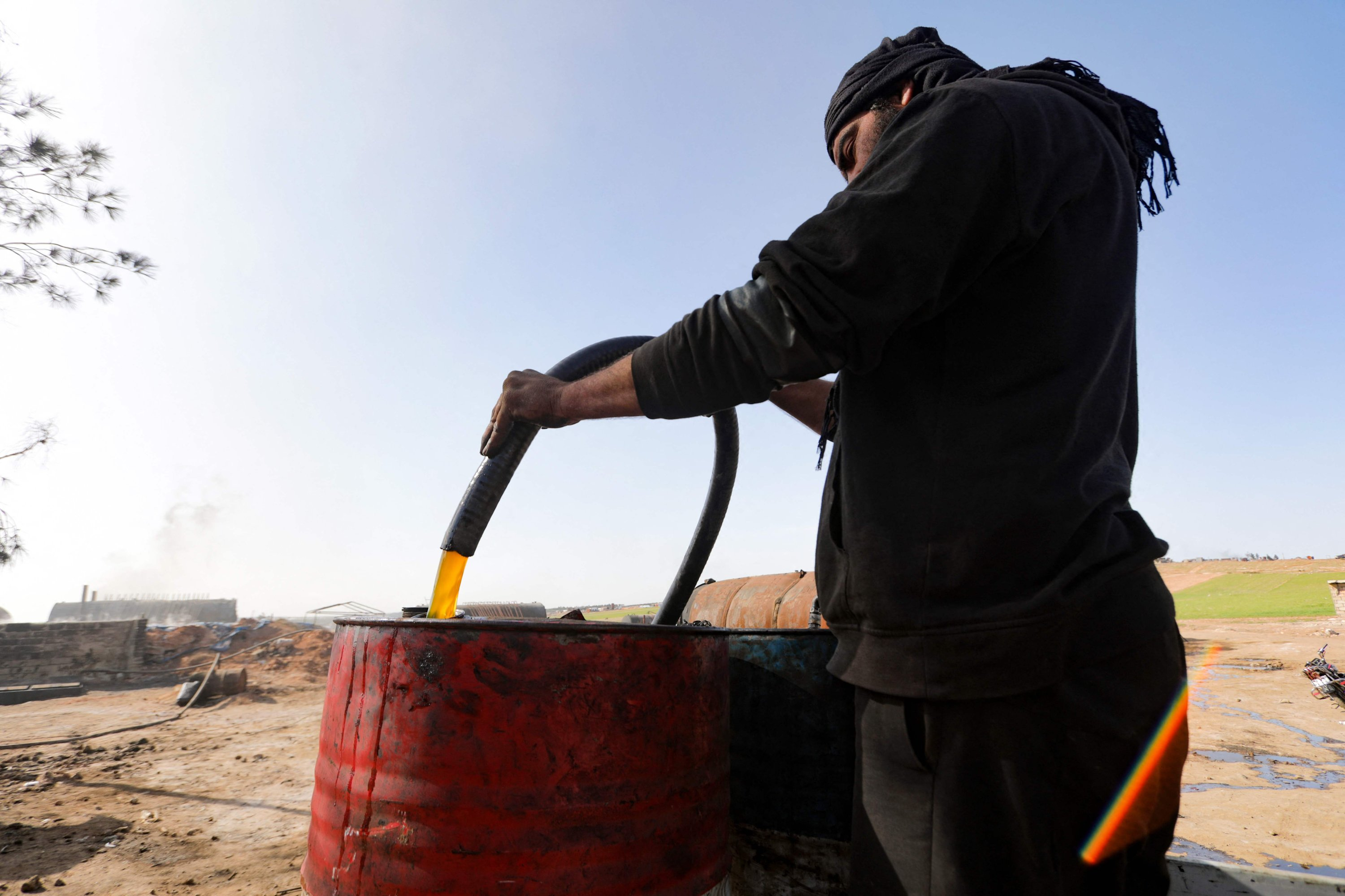 A displaced Syrian man works at a makeshift oil refinery near the village of Tarhin, in the northern countryside of Aleppo, Syria, Feb. 25, 2021. (Photo by Bakr ALKASEM / AFP)
