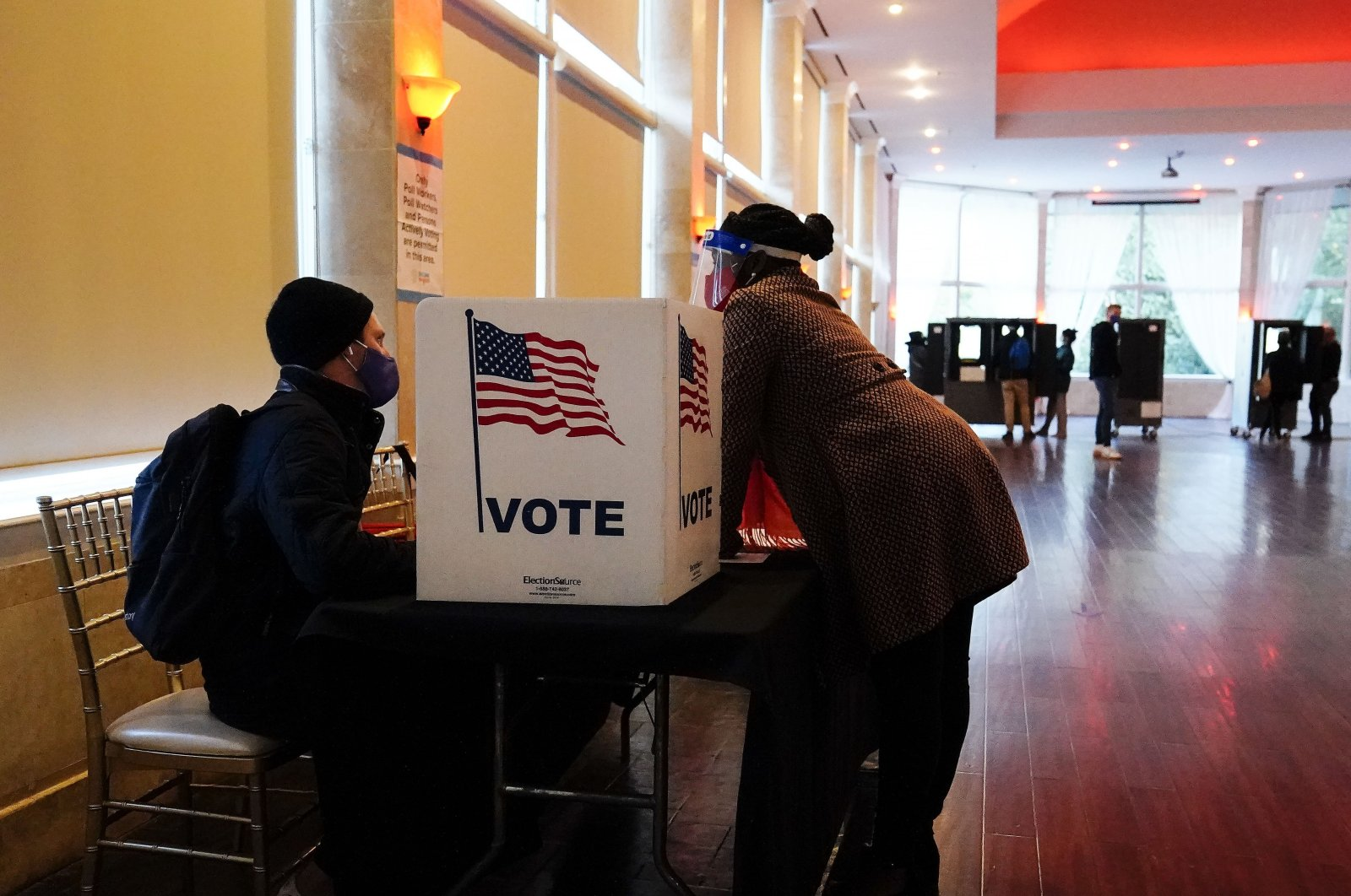 A poll worker talks to a voter before they vote on a paper ballot on Election Day in Atlanta, Georgia, Nov. 3, 2020. (AP Photo)