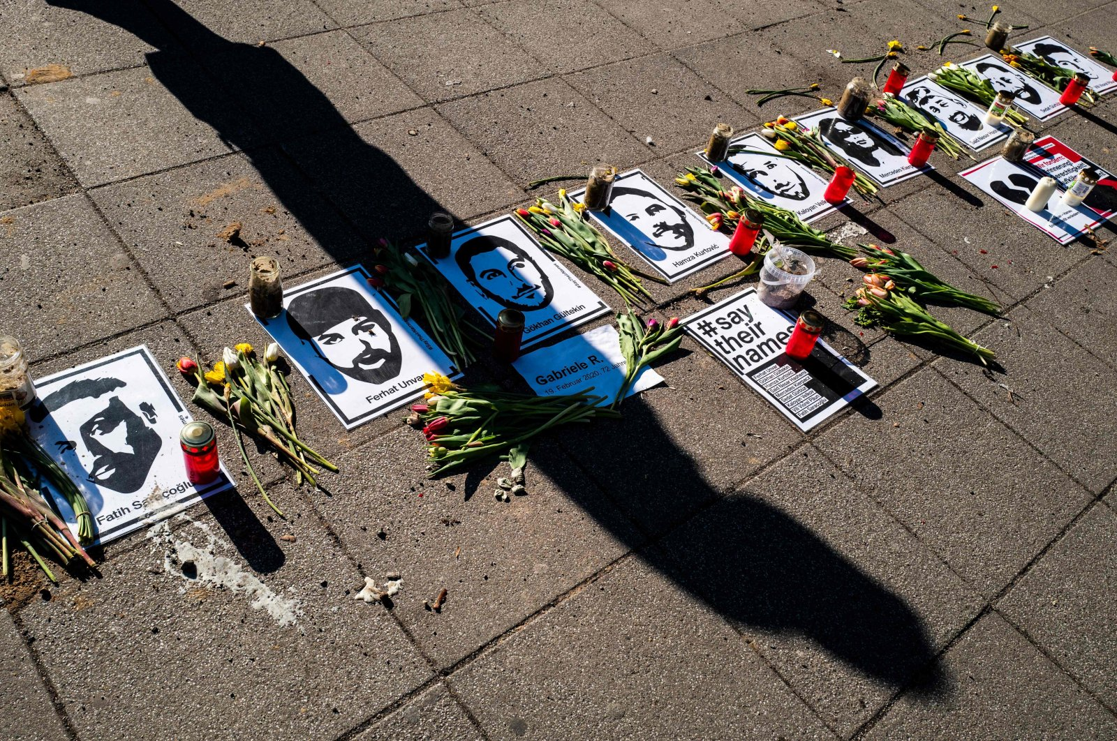 A passer-by casts a shadow on a makeshift memorial commemorating the nine victims of the deadly 2020 Hanau terrorist attack in front of a shopping mall in Berlin, Germany, March 2, 2021. (AFP Photo)