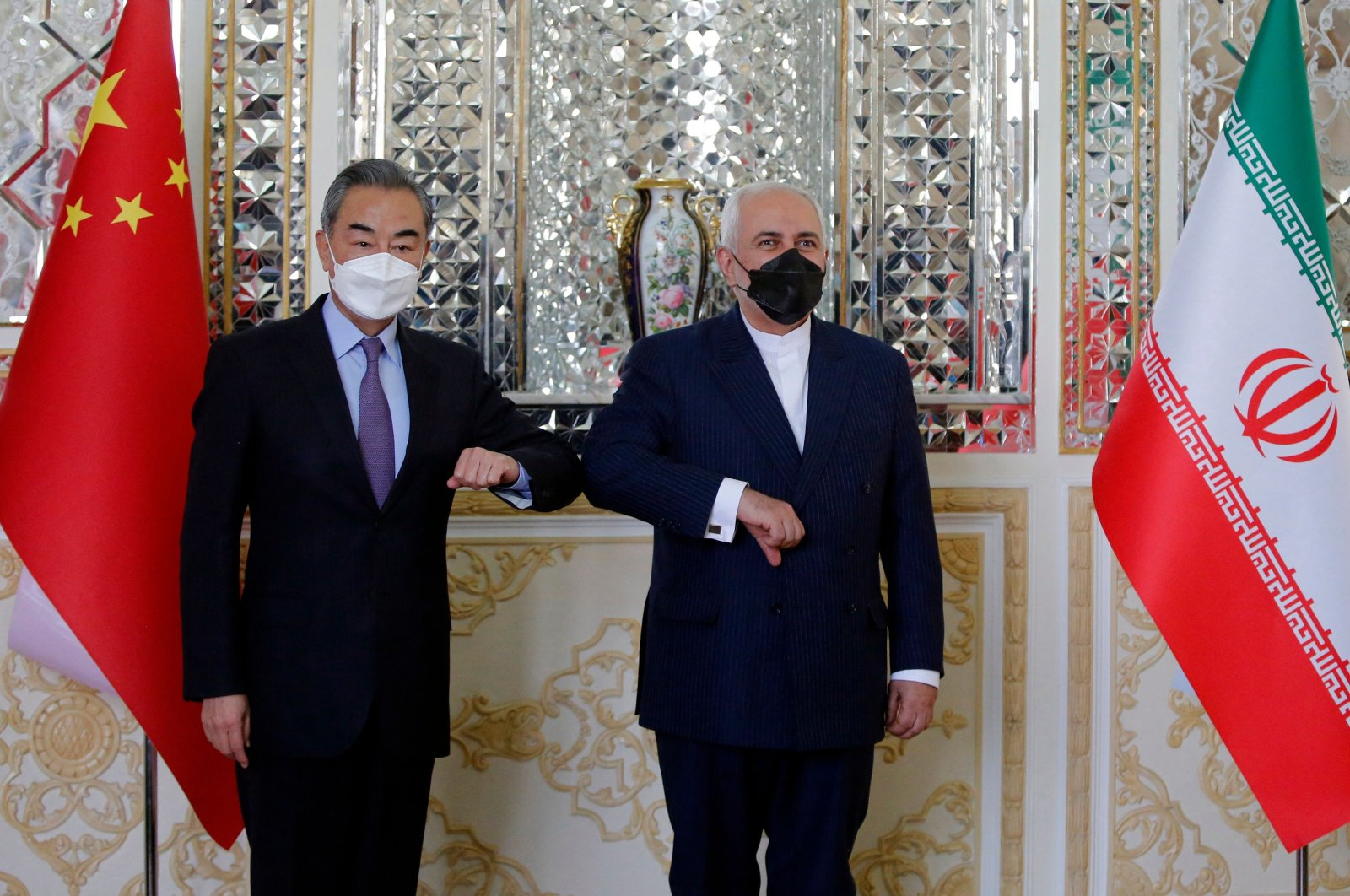 Iranian Foreign Minister Mohammad Javad Zarif (R) greets his Chinese counterpart Wang Yi, in Tehran, Iran, March 27, 2021. (AFP Photo)