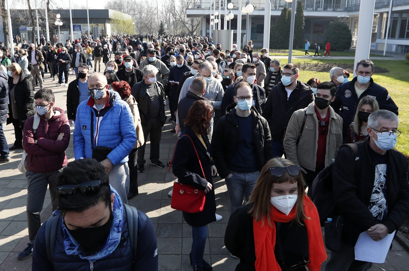 People wait in line to receive a dose of the AstraZeneca vaccine at the Belgrade Fair makeshift vaccination center in Belgrade, Serbia, March 27, 2021. (AP Photo)