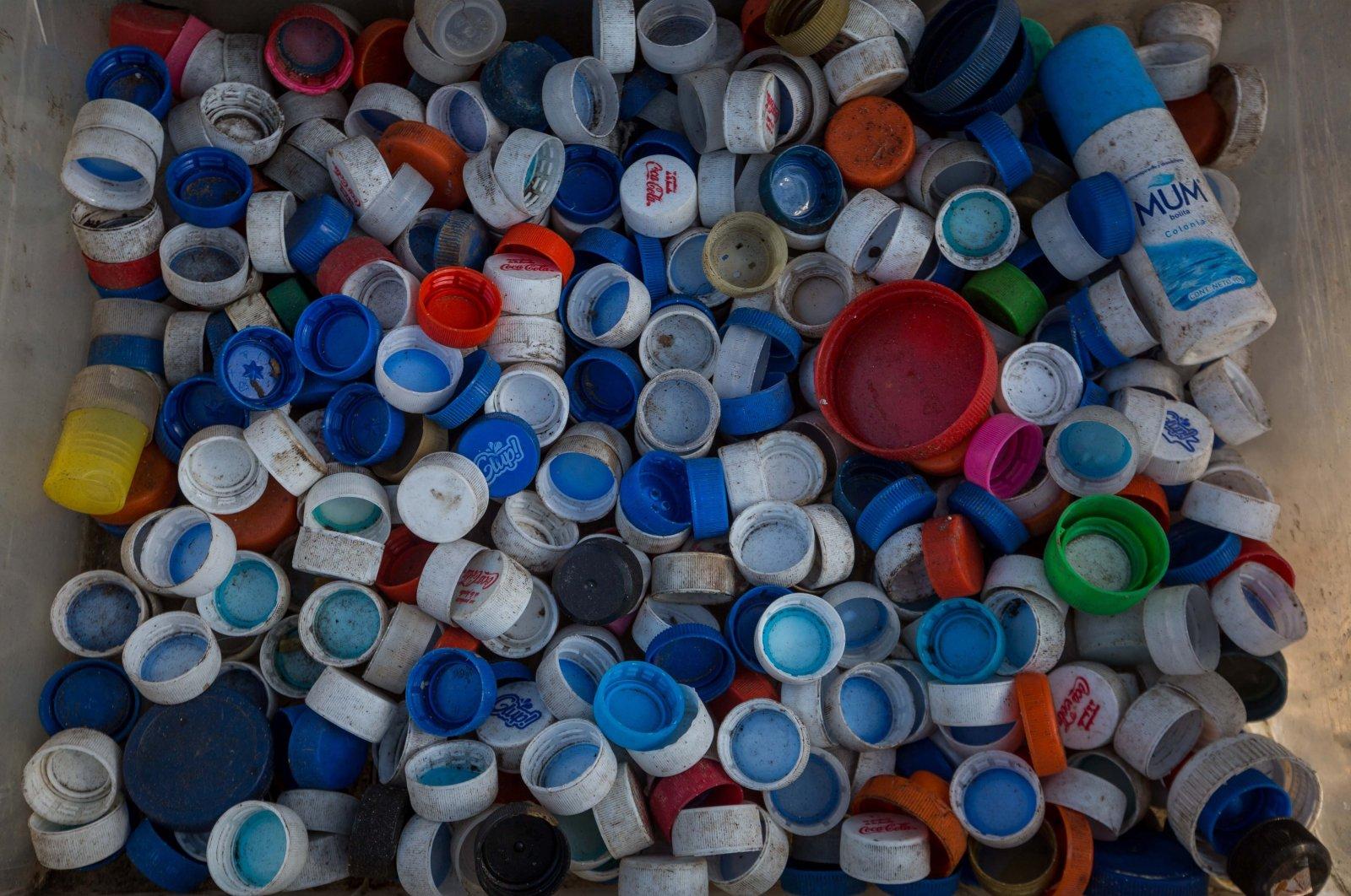 Plastic bottle caps in a box are seen in Caracas, Venezuela, March 04, 2021. (EPA Photo)