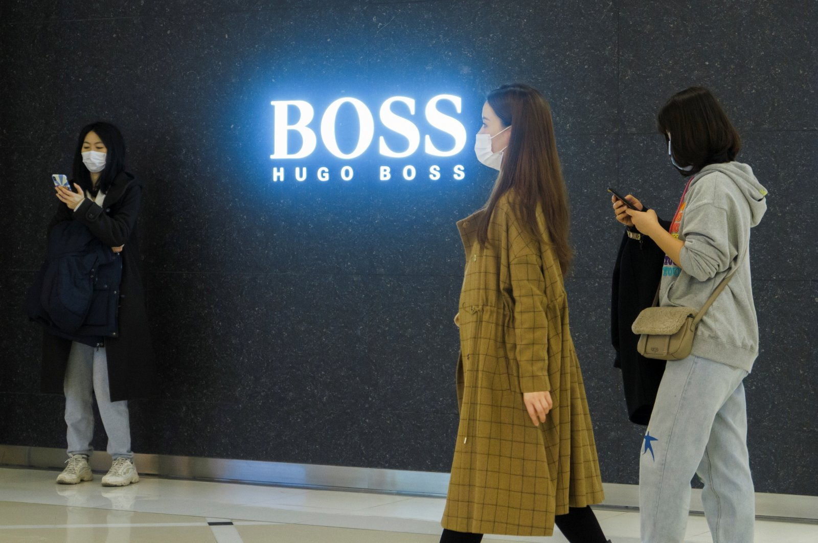People walk past a store of German fashion house Hugo Boss in Beijing, China, March 27, 2021. (Reuters Photo)