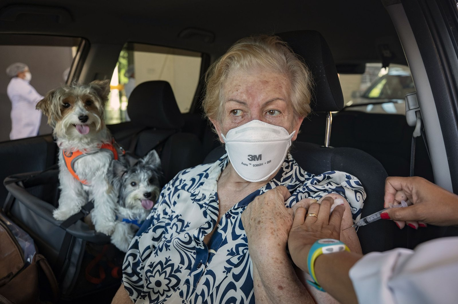 A woman gets a shot of the Sinovac COVID-19 vaccine while she sits in her car with her pets during a priority vaccination program for seniors at a drive-thru site set up in the Pacaembu soccer stadium parking lot in Sao Paulo, Brazil,  March 3, 2021. (AP Photo)