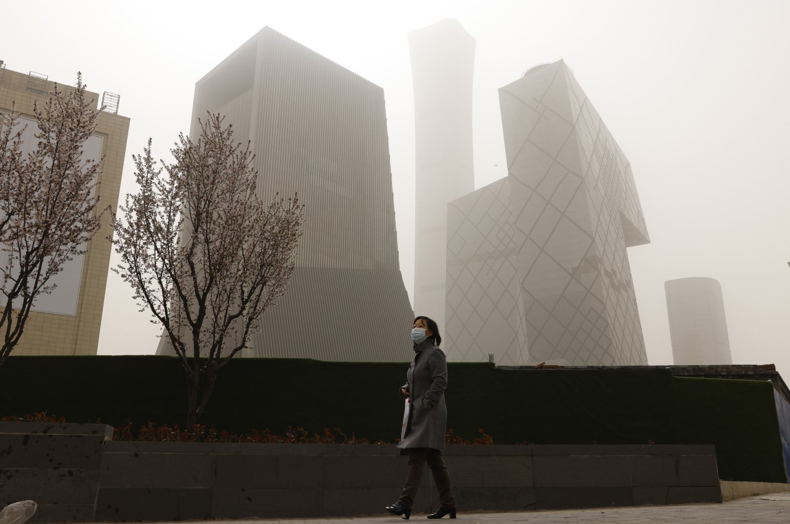 A woman walks near skyscrapers in the Central Business District during a sandstorm in Beijing, China, March 28, 2021. (AP Photo)