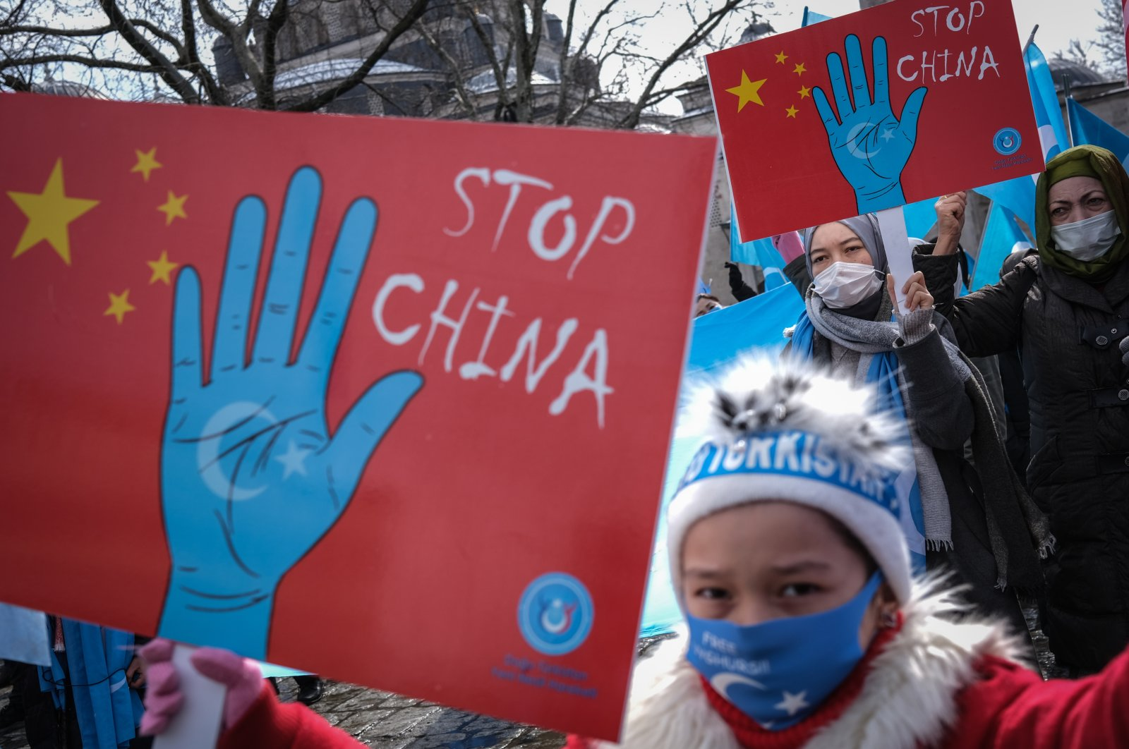 Uyghur protestors who have not heard from their families living in Xinjiang hold placards and Uyghur flags during a protest against China, in Istanbul, Turkey, March 25, 2021. (EPA Photo)
