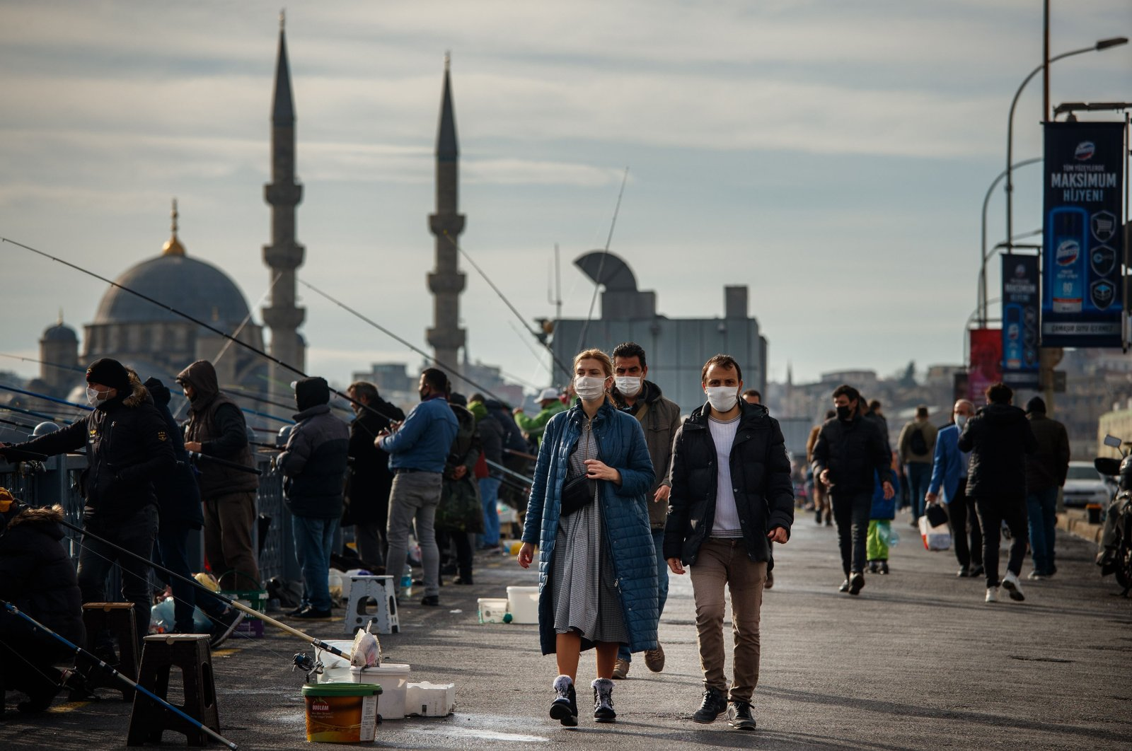 People in masks walk past fishermen during the COVID-19 pandemic, Istanbul, Turkey, Dec. 29, 2020. (Shutterstock Photo)
