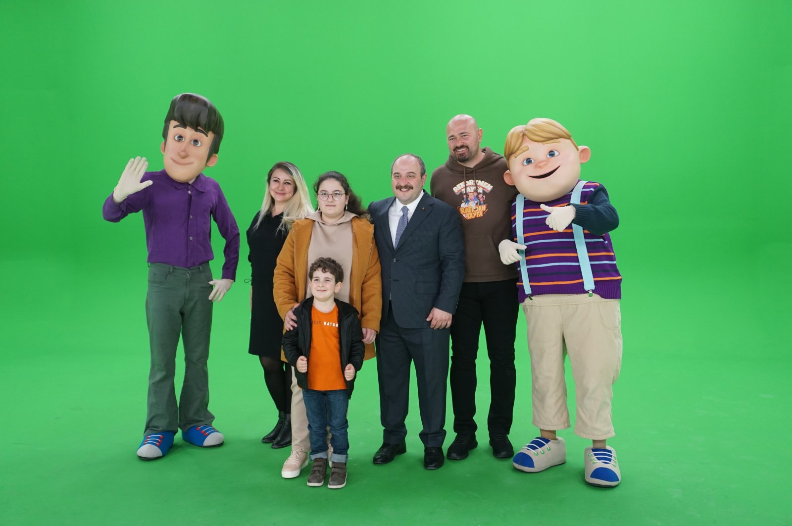 """Industry and Technology Minister Mustafa Varank (C), his two children and """"Rafadan Tayfa"""" producer Ismail Fidan (2nd R) pose with studio employees dressed as famous animated characters, Ankara, Turkey, March 28, 2021. (Photo by Industry and Technology Ministry via AA)"""
