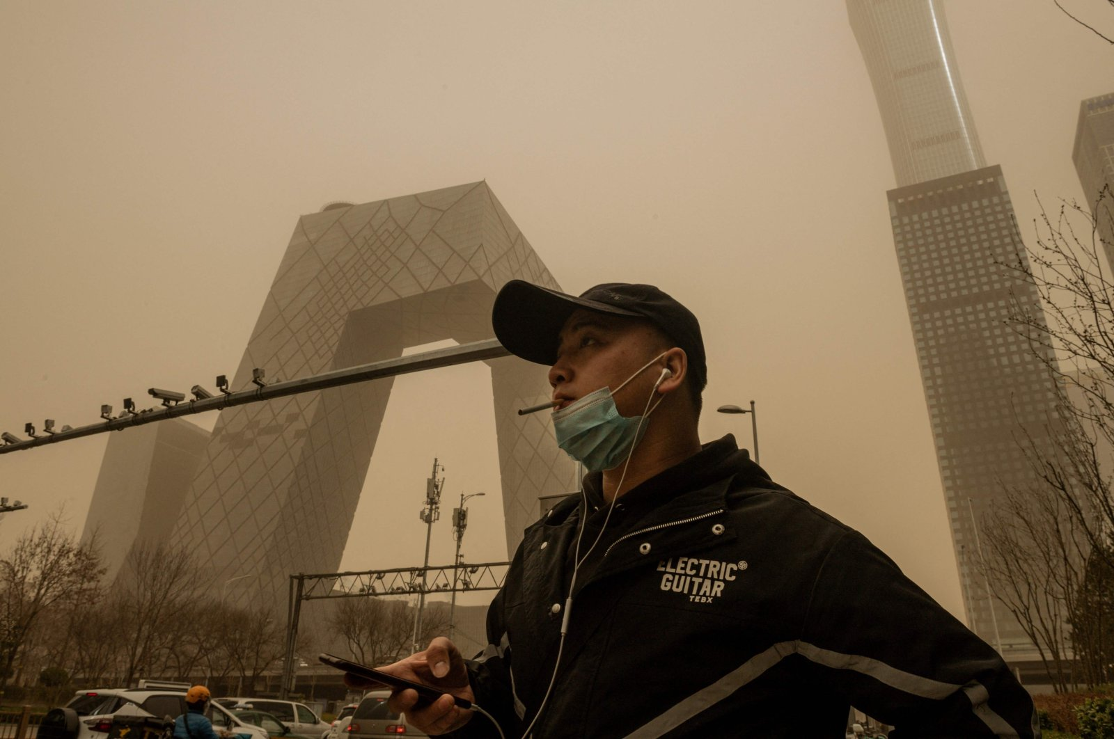 A man walks on a street smoking a cigarette during a sandstorm in the financial district in Beijing, China, March 15, 2021. (AFP Photo)