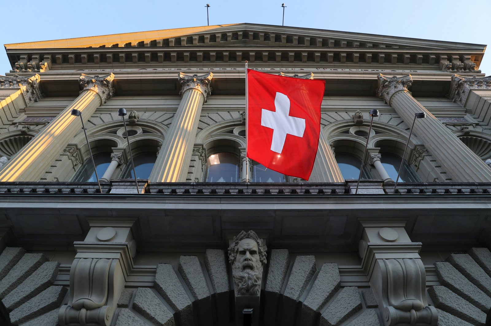 Switzerland's national flag flies at the Swiss Federal Palace (Bundeshaus), the seat of the parliament and the government, in Bern, Switzerland, March 18, 2021. (Reuters Photo)