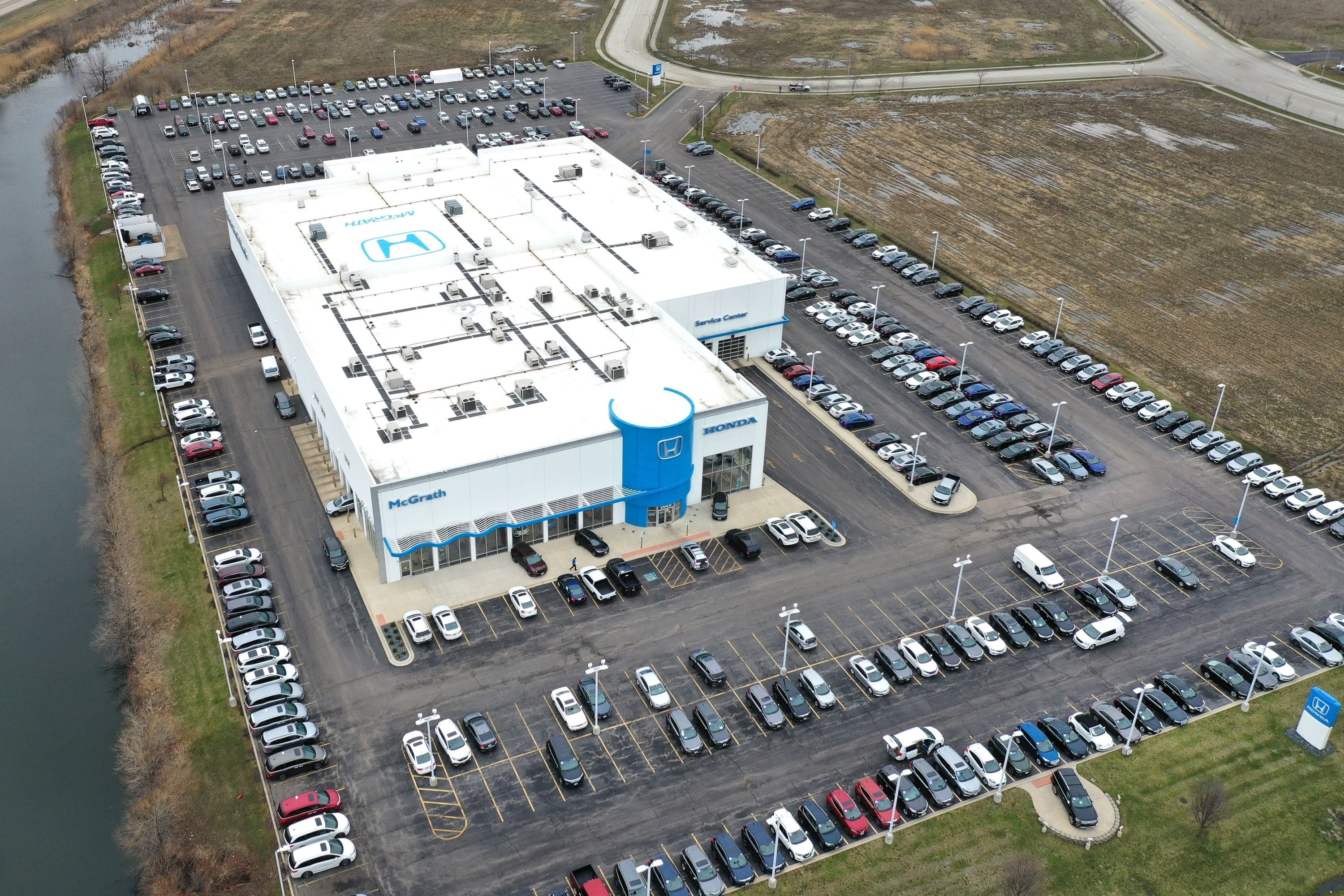 An aerial photo taken from a drone shows cars sitting on the lot at the McGrath Honda dealership on in Elgin, Illinois, U.S.,  March 25, 2021. (Getty Images via AFP)