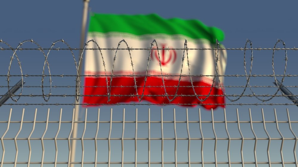 Blurred waving flag of Iran behind a barbed-wire fence. (Shutterstock Photo)