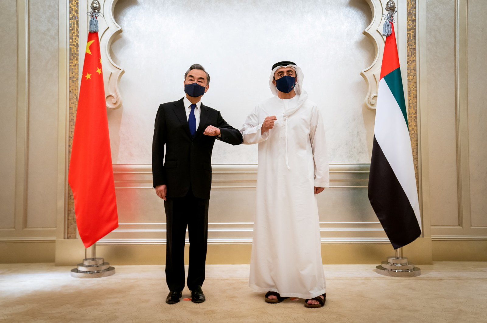 Chinese State Councilor and Foreign Minister Wang Yi (L) and UAE Foreign Minister Abdullah Bin Zayed Al Nahyan do an elbow shake during their meeting in Abu Dhabi, United Arab Emirates, March 28, 2021. (REUTERS Photo)
