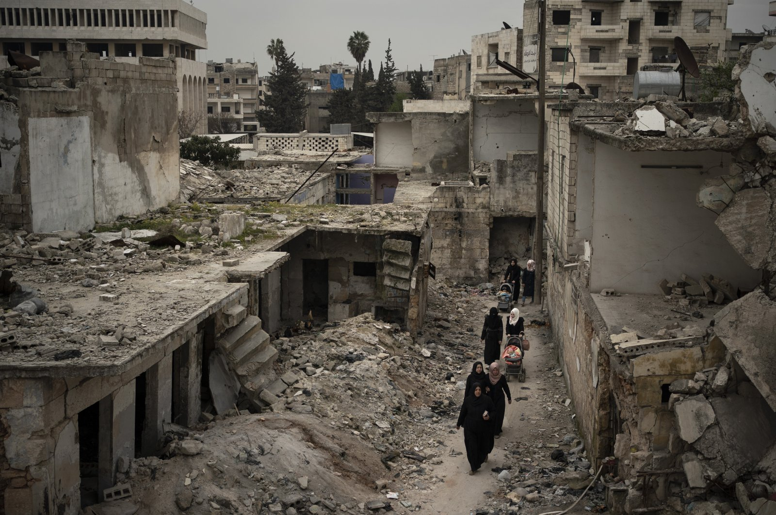 Women walk in a neighborhood heavily damaged by airstrikes in Idlib, Syria, March 12, 2020. (AP File Photo)