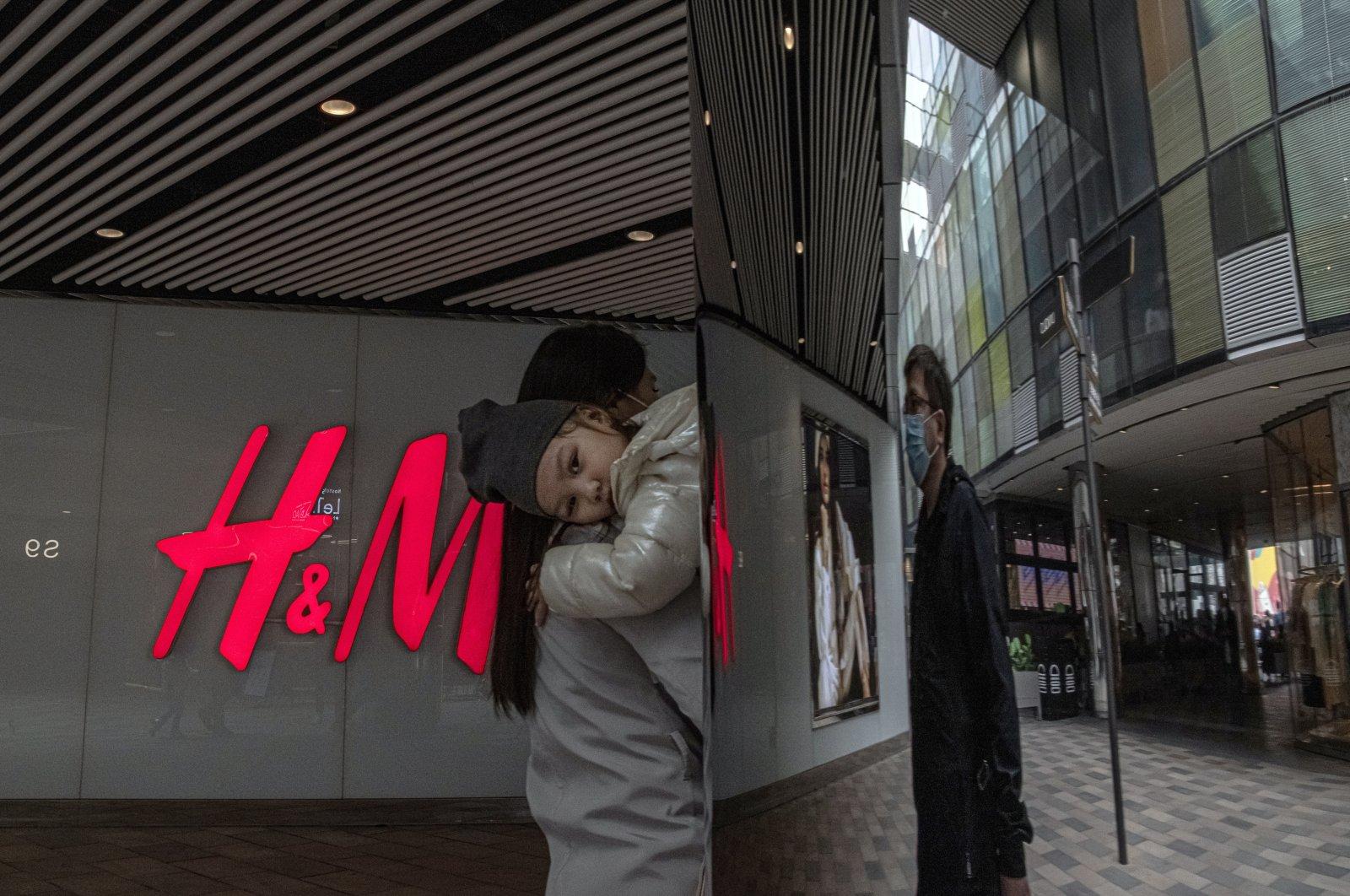 Eine Frau mit einem Kind geht am 27. März 2021 in einem Einkaufsviertel von Sanlitun in Peking, China, an einem H&M-Geschäft vorbei. (EPA-Foto)