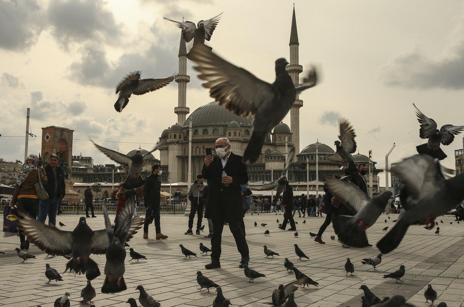 A man feeds pigeons amid the coronavirus pandemic, at Taksim Square, Istanbul, Turkey, March 25, 2021. (AP Photo)