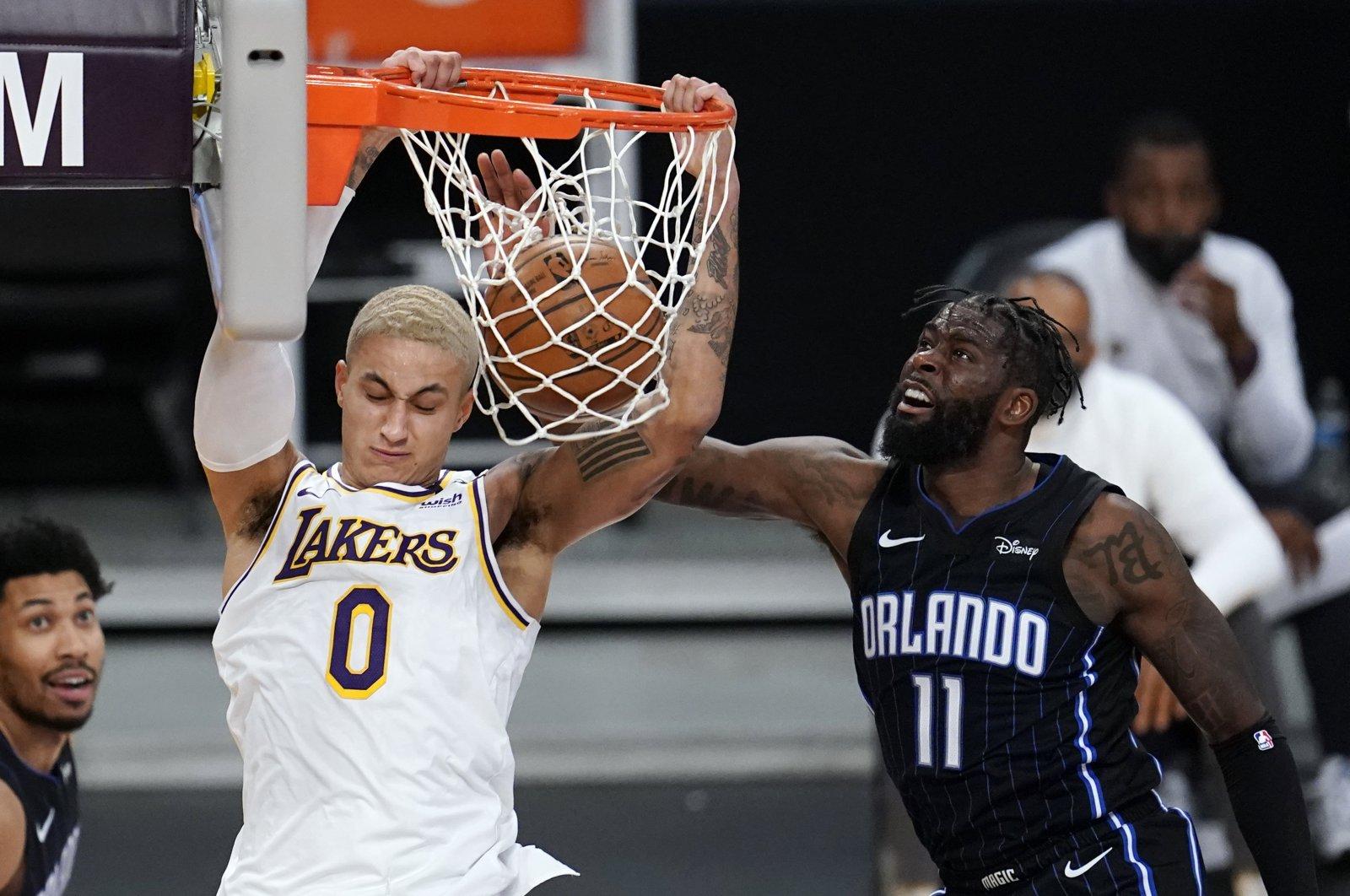 Los Angeles Lakers forward Kyle Kuzma (L) dunks past Orlando Magic forward James Ennis III during an NBA game, Los Angeles, California, U.S., March 28, 2021. (AP Photo)