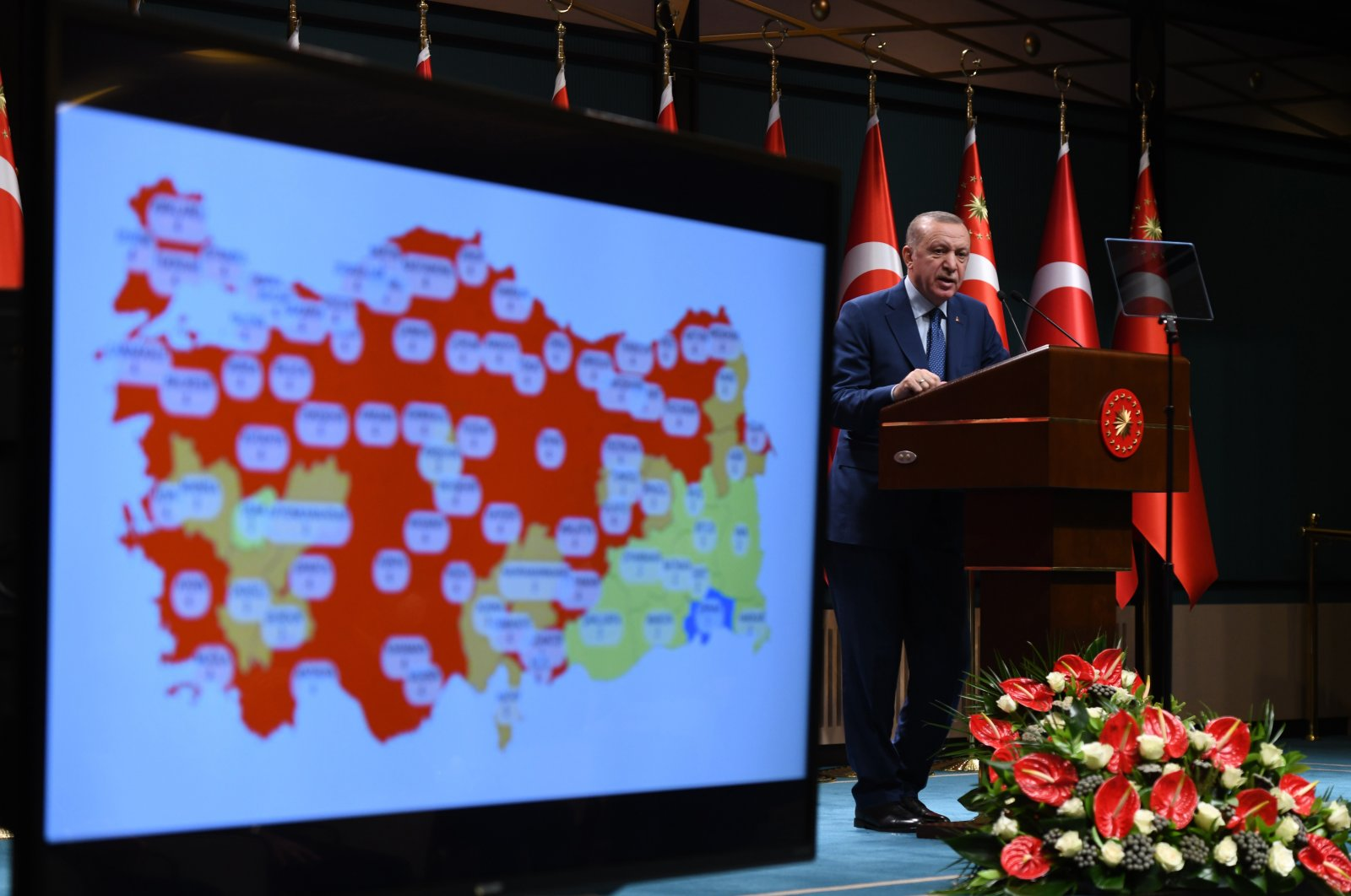 A color-coded map on the current state of the coronavirus pandemic in Turkey is seen alongside President Recep Tayyip Erdoğan, who is speaking during a press conference in the Presidential Complex in Ankara, Turkey, March 29, 2021. (IHA Photo)