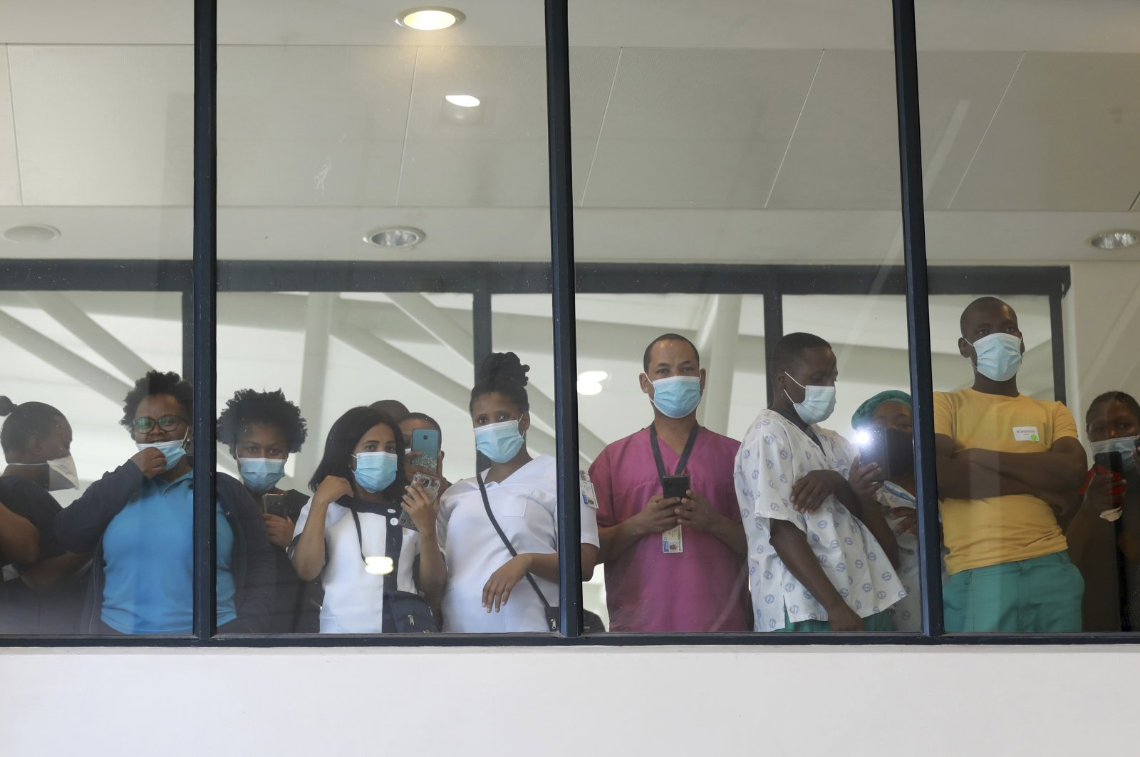 Health care workers look through a window at a hospital during the rollout of the first batch of Johnson and Johnson vaccines in the country, in Khayelitsha, Cape Town, South Africa, Feb. 17, 2021. (AP Photo)
