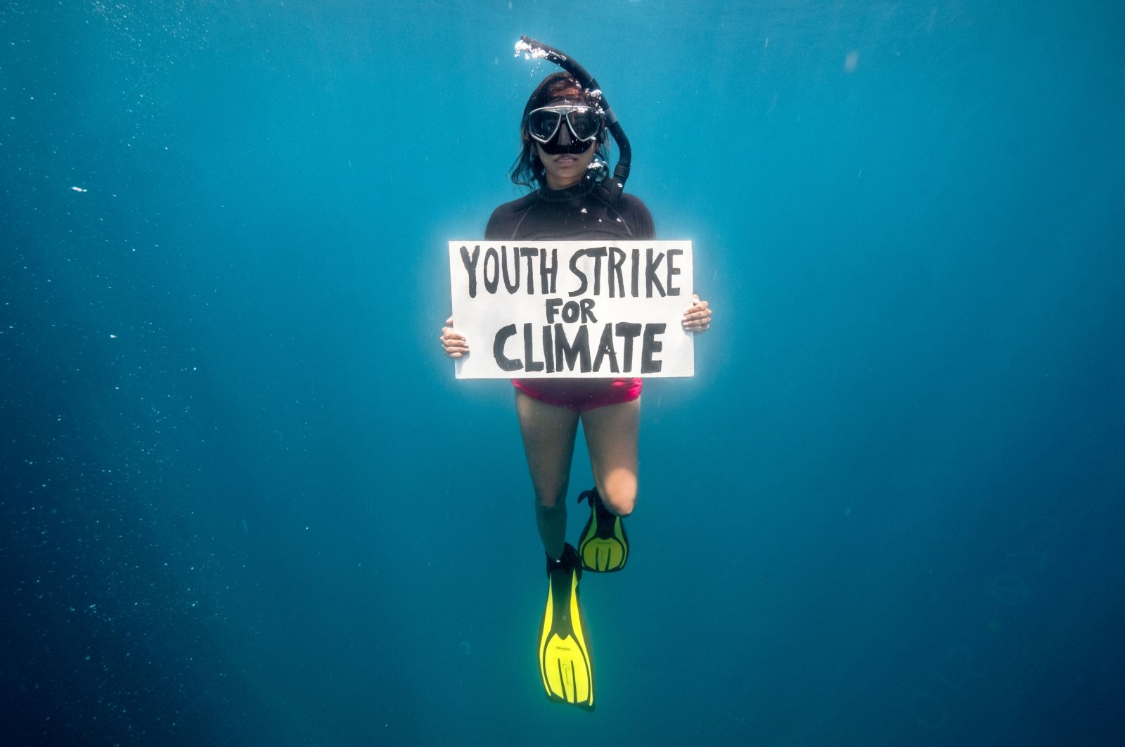 """Mauritian scientist and climate change activist Shaama Sandooyea 24, holds a placard reading """"Youth Strike For Climate,"""" during an underwater protest at the Saya de Malha Bank to highlight the need to protect the world's largest seagrass meadow within the Mascarene plateau, Mauritius, March 6, 2021. (Reuters Photo)"""