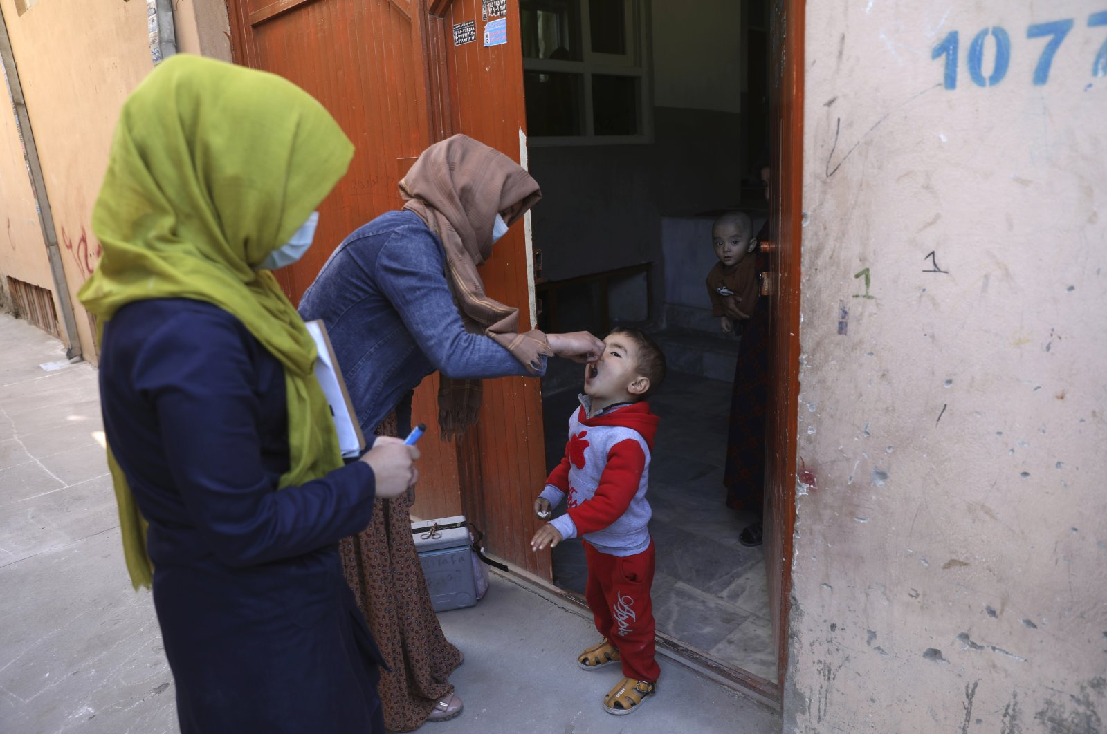 Health workers administer a polio vaccine to a child during a door-to-door polio vaccination campaign in the city of Kabul, Afghanistan, March 30, 2021. (AP Photo)