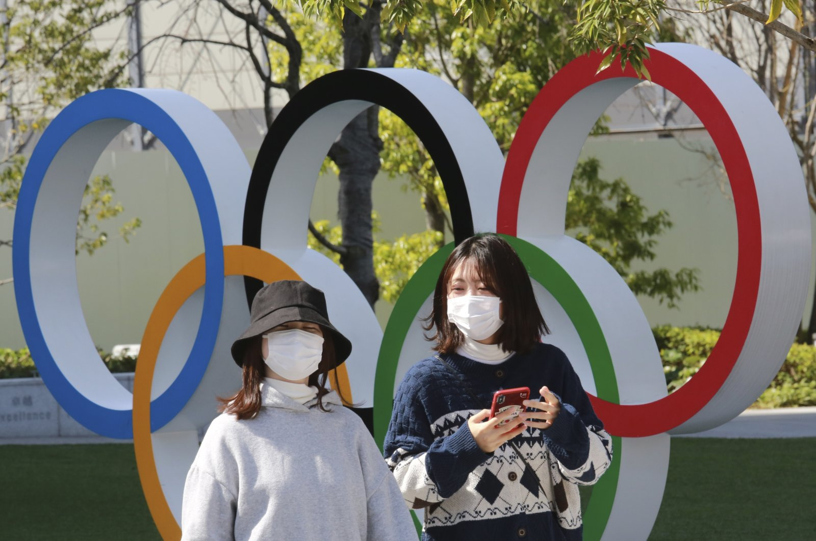 People wearing protective facemask walk past the Olympic rings in Tokyo, Japan, March 17, 2021 (AP Photo)