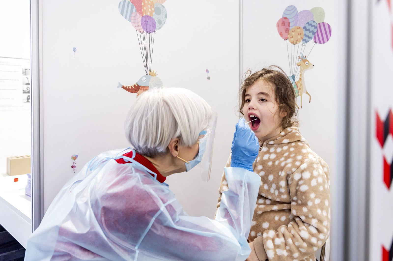 A health worker collects a throat swab sample from a child to test for COVID-19 at a special children's testing center in Amsterdam, the Netherlands, March 26, 2021. (AFP Photo)