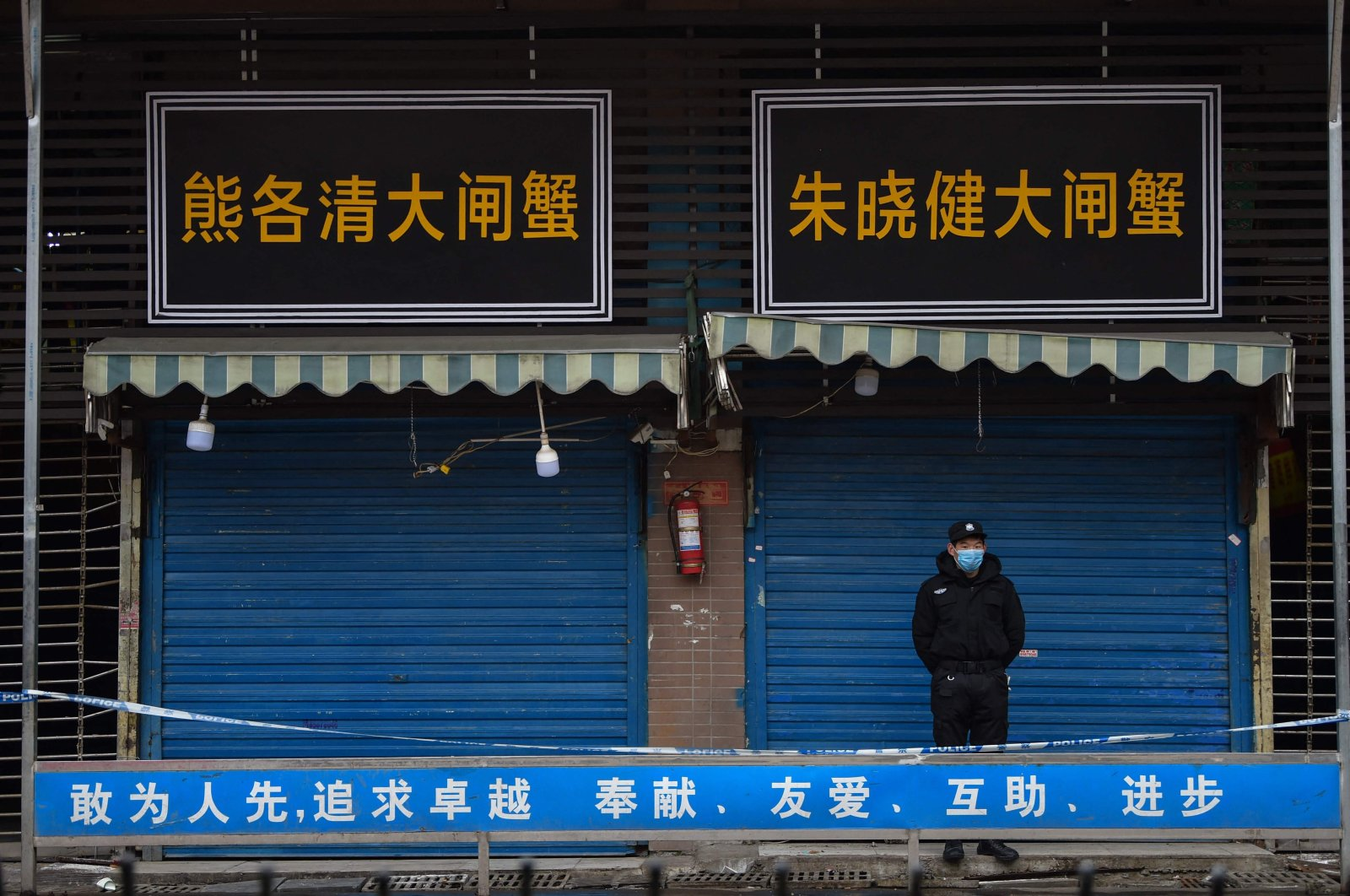 A security guard stands outside the Huanan Seafood Wholesale Market where the coronavirus was detected in Wuhan, China, Jan. 24, 2020. (Photo by Hector RETAMAL / AFP)