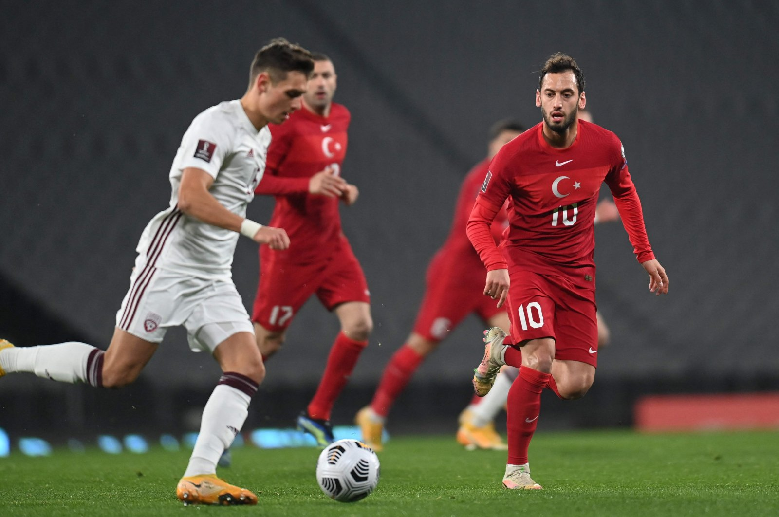 Latvia's forward Vladislavs Fjodorovs (L) runs with the ball in front of Turkey's midfielder Hakan Çalhanoğlu (R) during the FIFA World Cup Qatar 2022 qualification Group G football match between Turkey and Latvia at the Olympic Stadium, in Istanbul, on March 30, 2021. (AFP Photo)