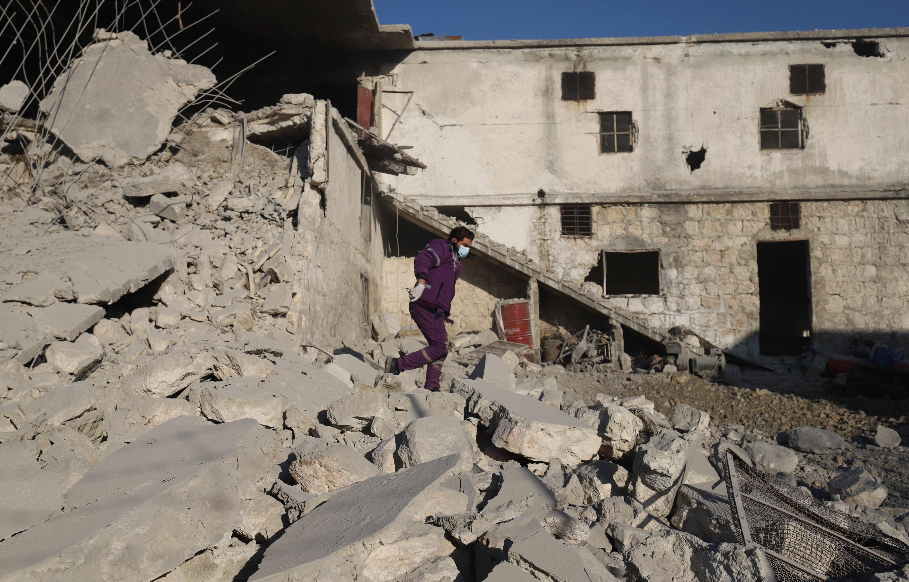 A Syrian man walks amid the rubble of a destroyed building following reported Russian airstrikes on the outskirts of the opposition-held northwestern city of Idlib, Syria, March 29, 2021. (Photo by Abdulaziz Ketaz via AFP)