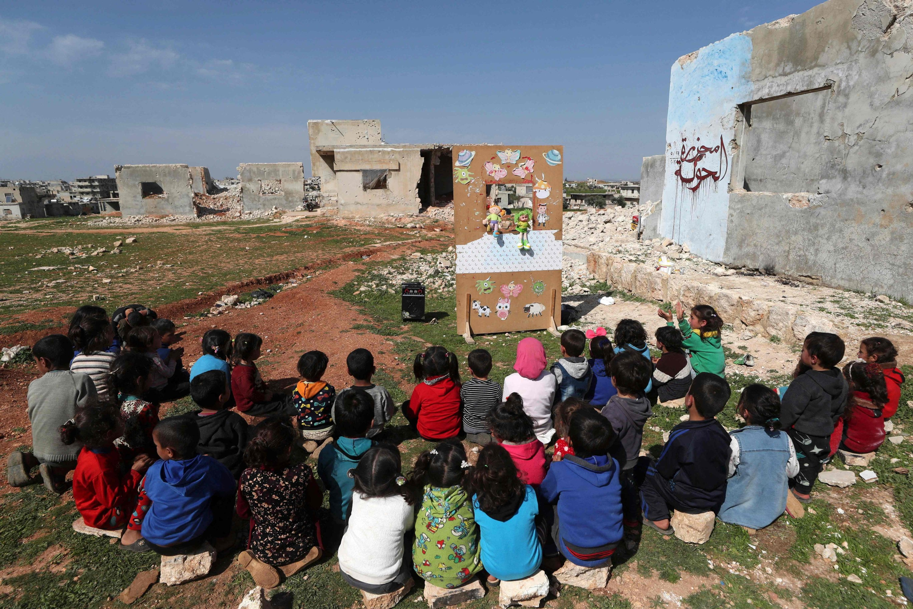 Syrian children watch a puppet show performed by a local theater group amid the ruins of buildings destroyed during Syria's civil war, in al-Fua, in the country's northwestern Idlib, Syria, March 30, 2021. (Photo by Omar Haj Kadour via AFP)