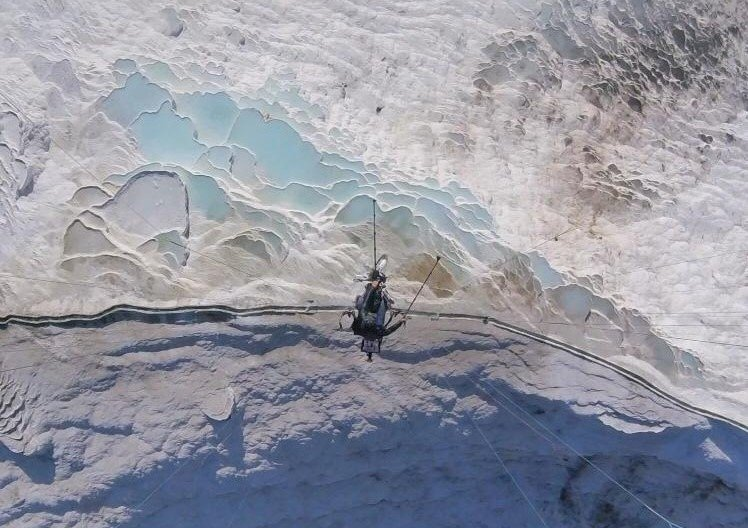 Hasan Kaval soars over Pamukkale in his paraglider in Denizli, southwestern Turkey, Macrh 30, 2021. (IHA Photo)