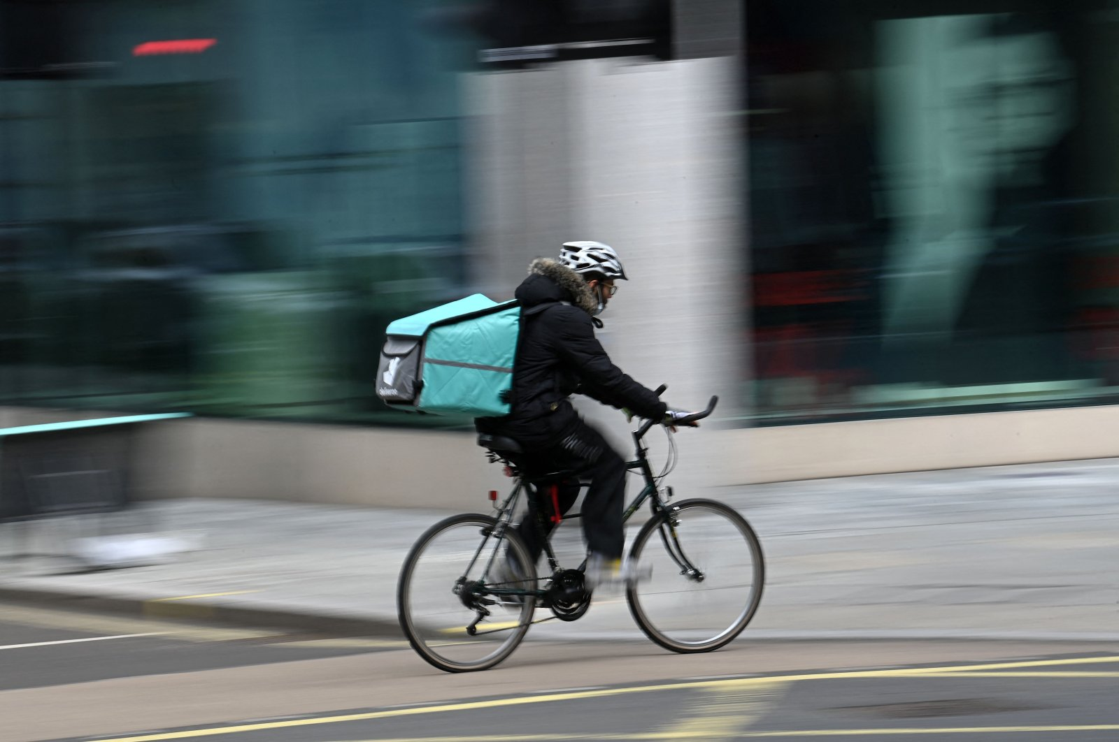 A Deliveroo rider cycles through central London, U.K., March 26, 2021. (AFP Photo)